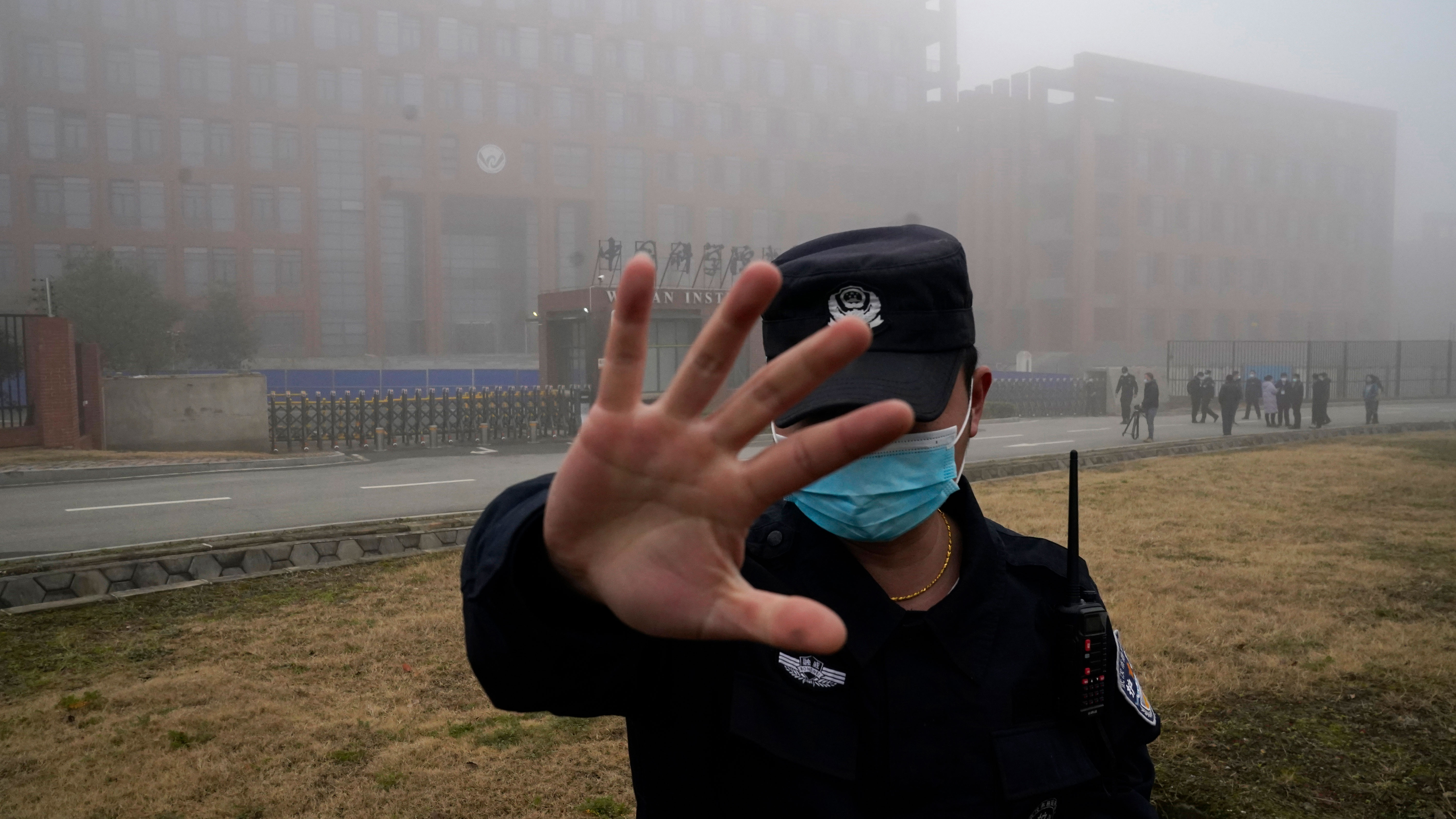 A security person moves journalists away from the Wuhan Institute of Virology after a World Health Organisation team arrived for a field visit in Wuhan in China's Hubei province in February 2021.