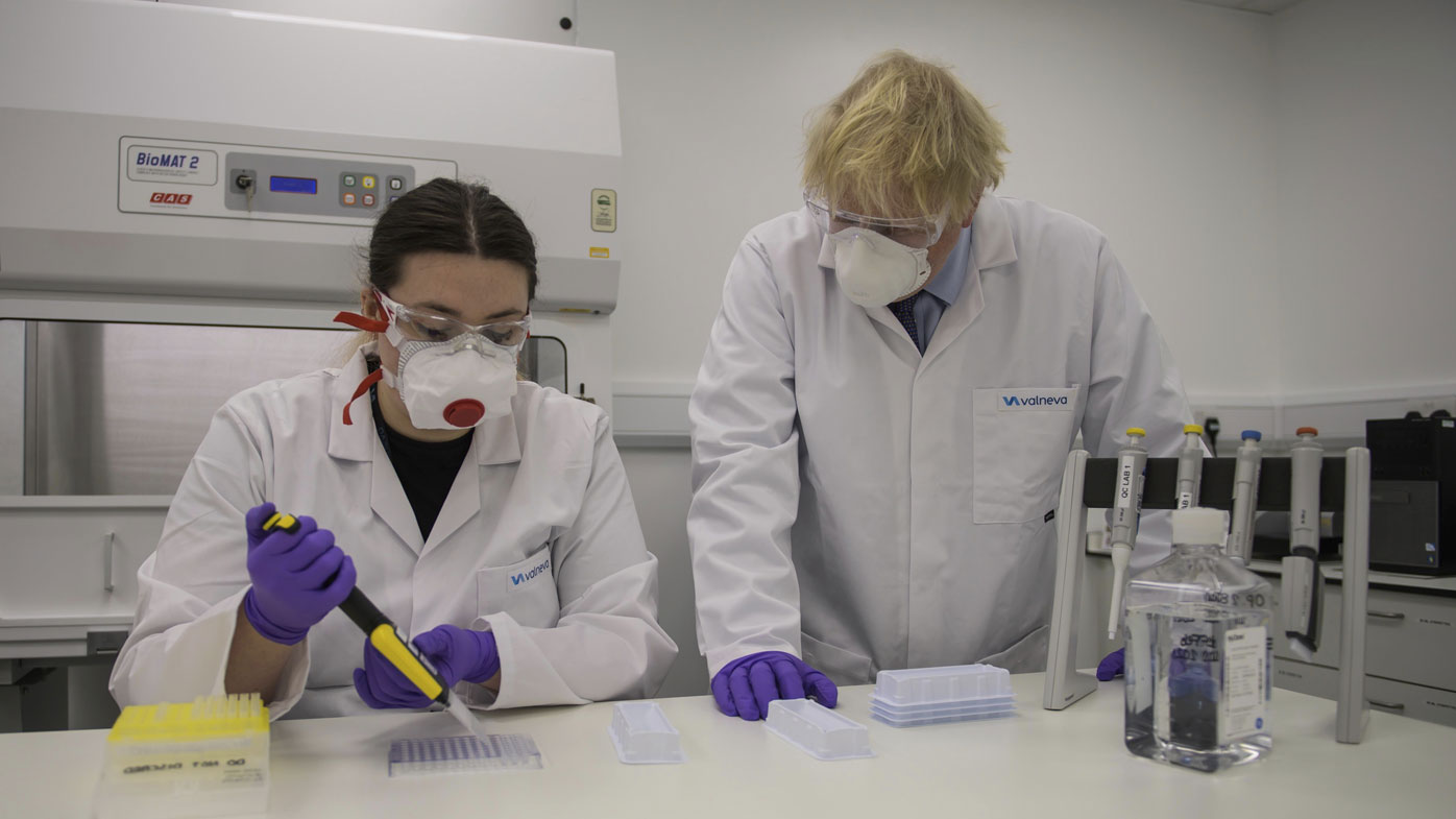 Britain's Prime Minister Boris Johnson with quality control technician Kerri Symington, visits the French biotechnology laboratory Valneva in Livingston, Scotland, Thursday Jan. 28, 2021, where they will be producing a COVID-19 vaccine on a large scale, during a visit to Scotland.