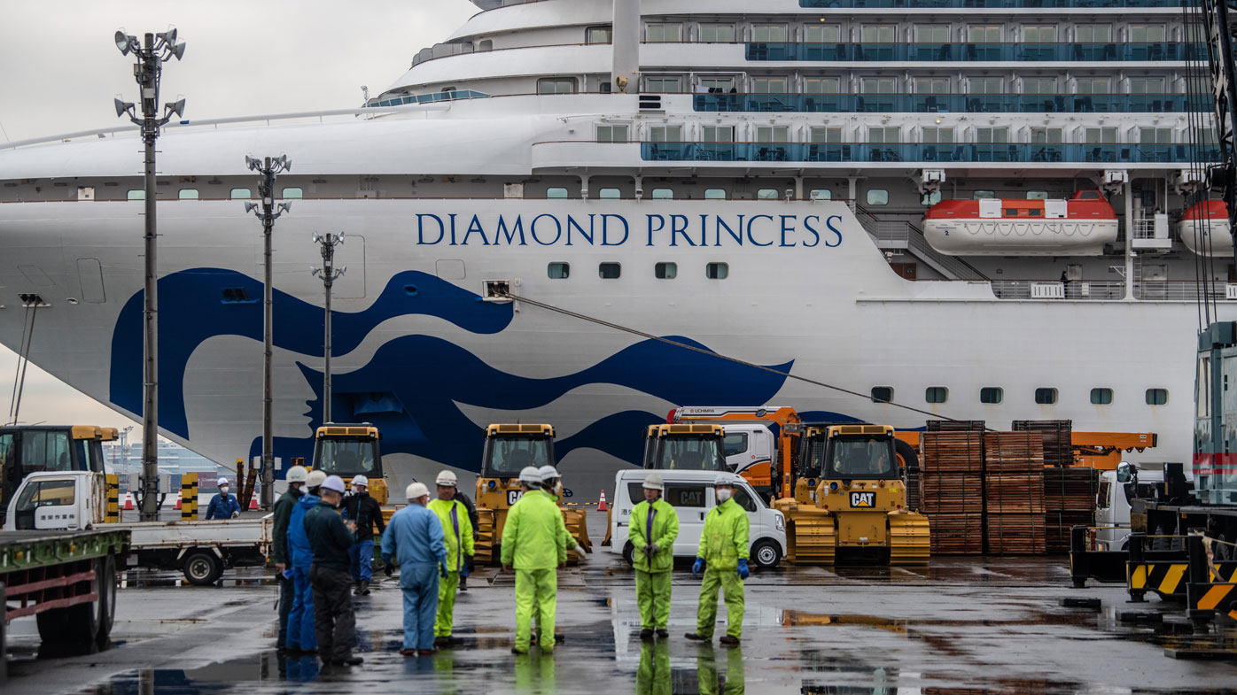 Workers gather on the dock next to the Diamond Princess cruise ship in Yokohama, Japan.