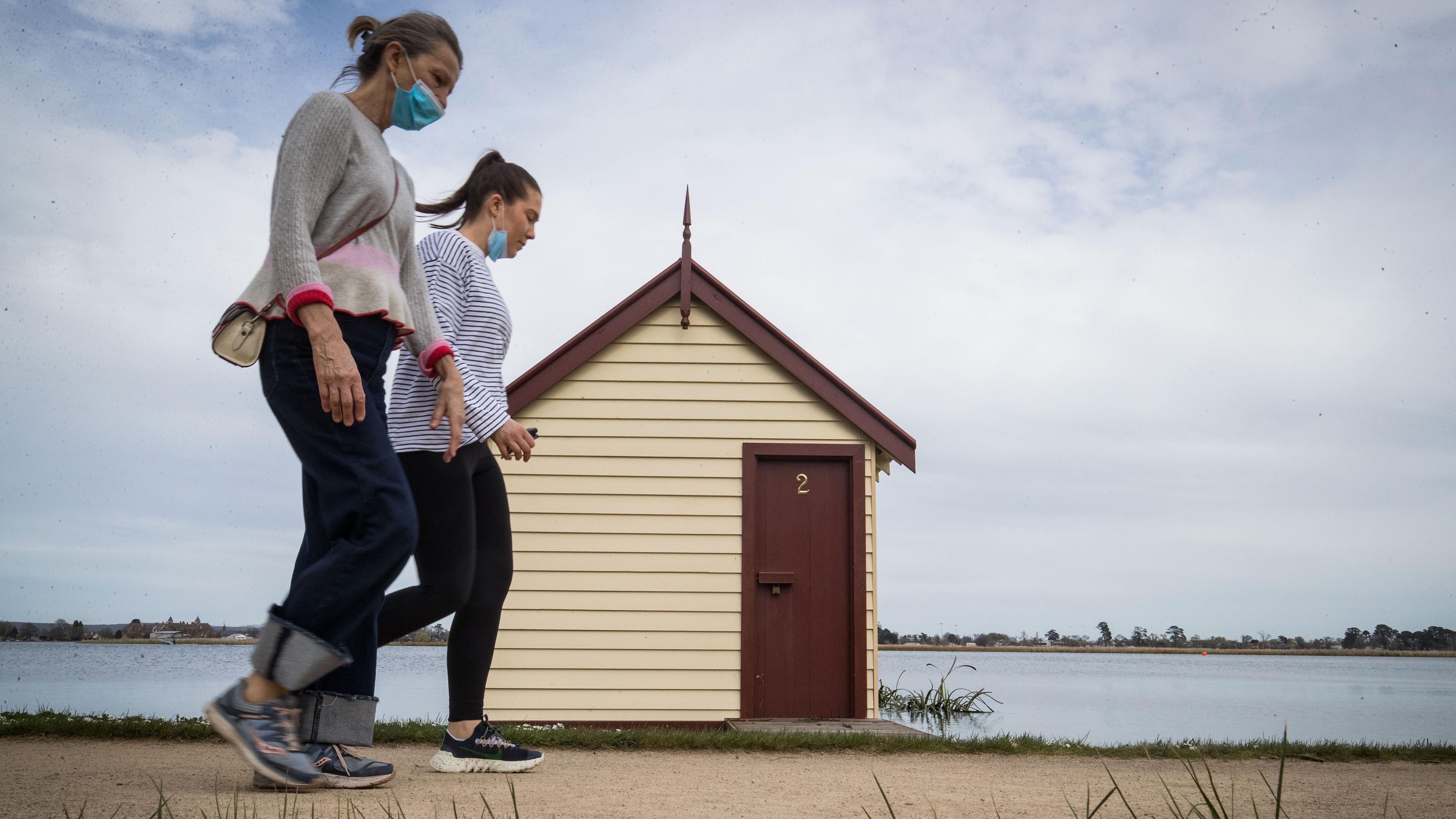 People walk around Lake Wendouree in Ballarat, Victoria, where restrictions have eased.