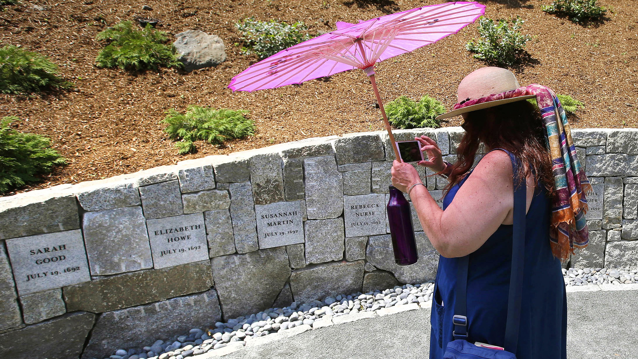Karla Hailer, a fifth-grade teacher from Scituate, Mass., shoots a video where a memorial stands at the site in Salem, Mass., where five women were hanged as witches.
