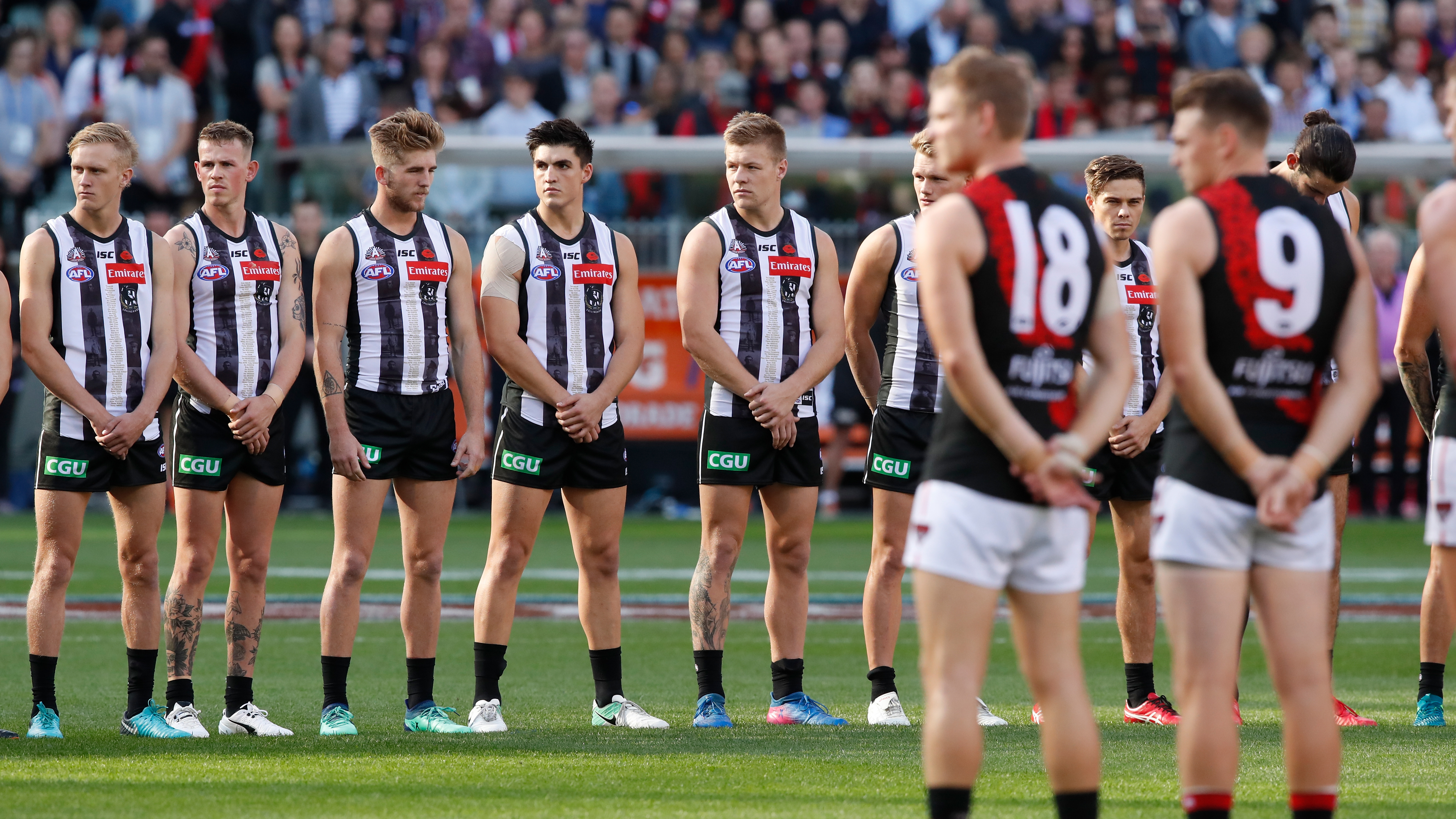 Collingwood and Essendon players line up at the start of an Anzac Day match.