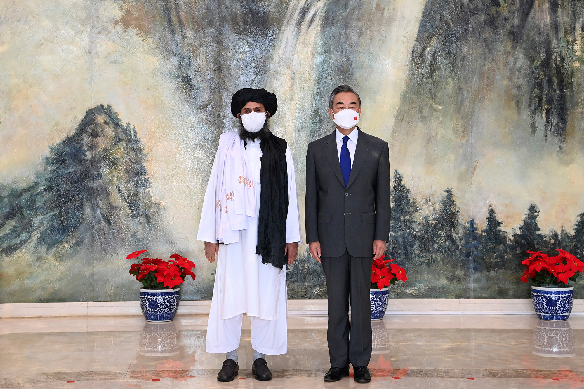 FILE - In this  July 28, 2021, file photo released by China's Xinhua News Agency, Taliban co-founder Mullah Abdul Ghani Baradar, left, and Chinese Foreign Minister Wang Yi pose for a photo during their meeting in Tianjin, China. China has expressed a willingness to hold talks with the U.S. to promote a soft landing in Afghanistan, while heavily criticizing Washington and again demanding that the Biden administration halt its attacks on China. (Li Ran/Xinhua via AP, File)