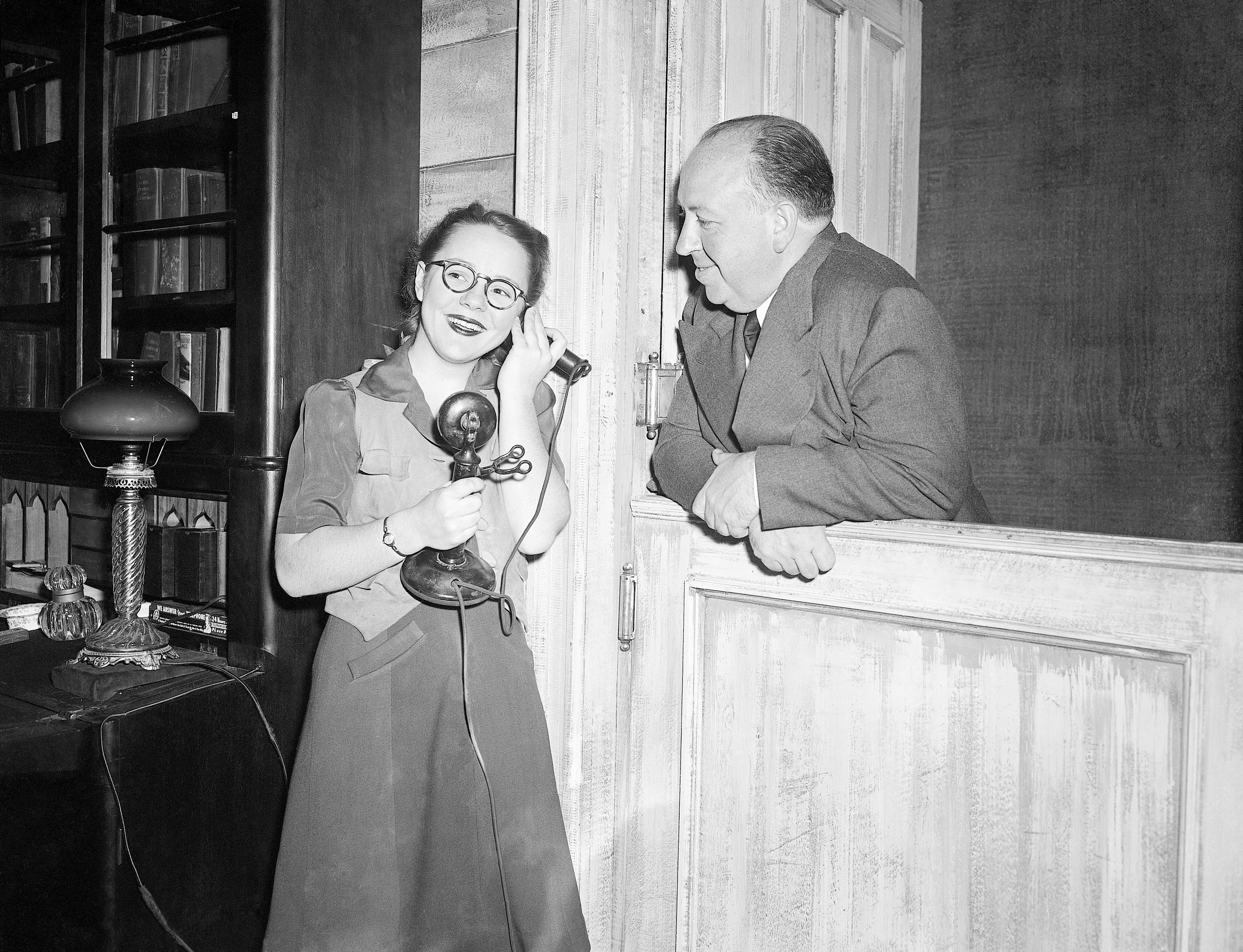 Alfred Hitchcock smiles as he watches his daughter Pat, 15, answer the phone during rehearsal for Violet, in which she plays the title role in 1944.