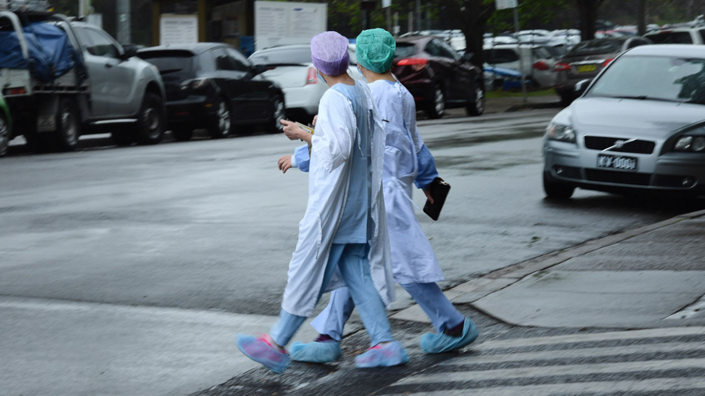 Health workers cross the road near Concord Repatriation General Hospital in Concord, NSW.
