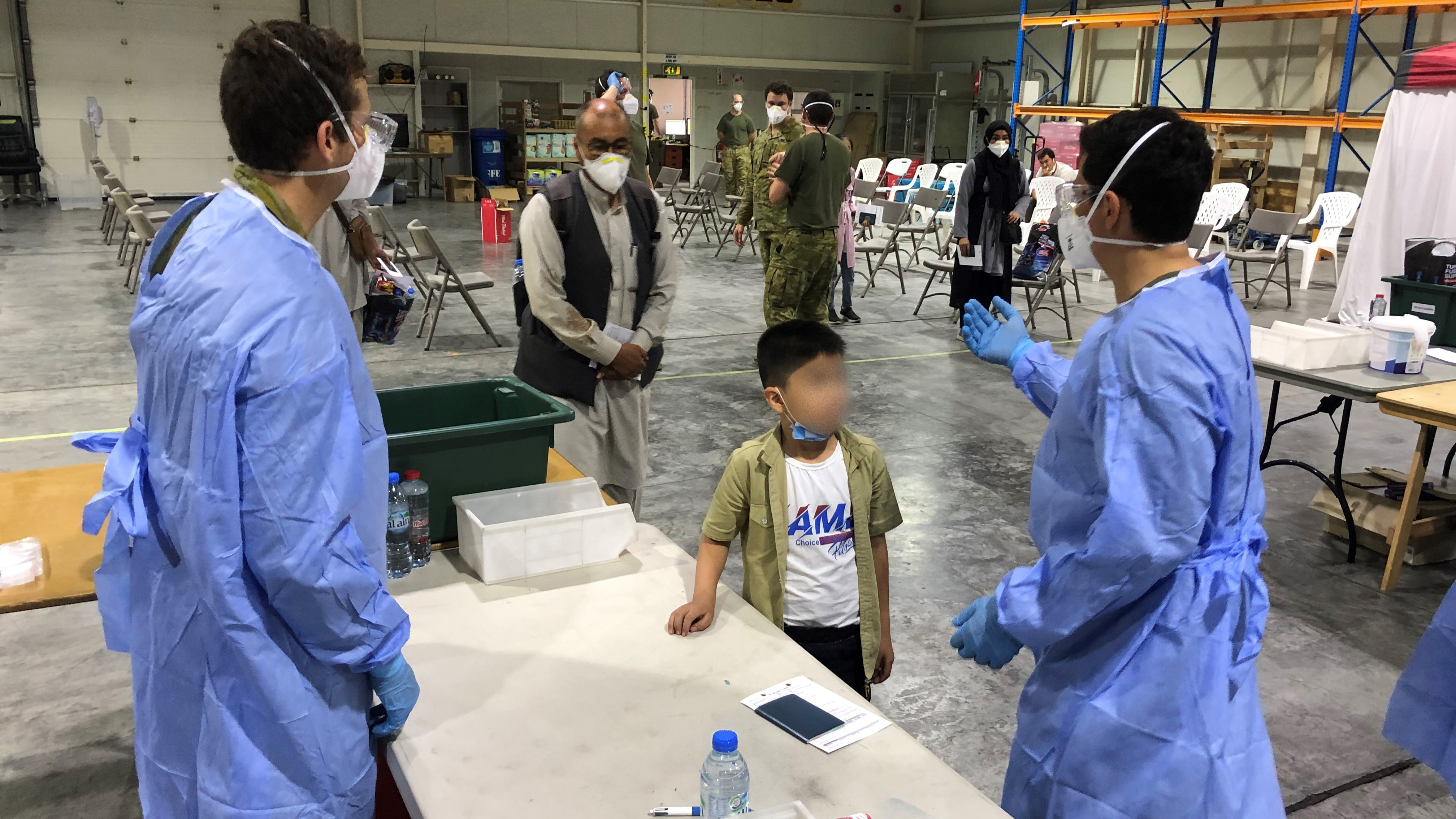 Australian Defence Force personnel process the first evacuees from Kabul, Afghanistan at Australia's main base in the Middle East region.