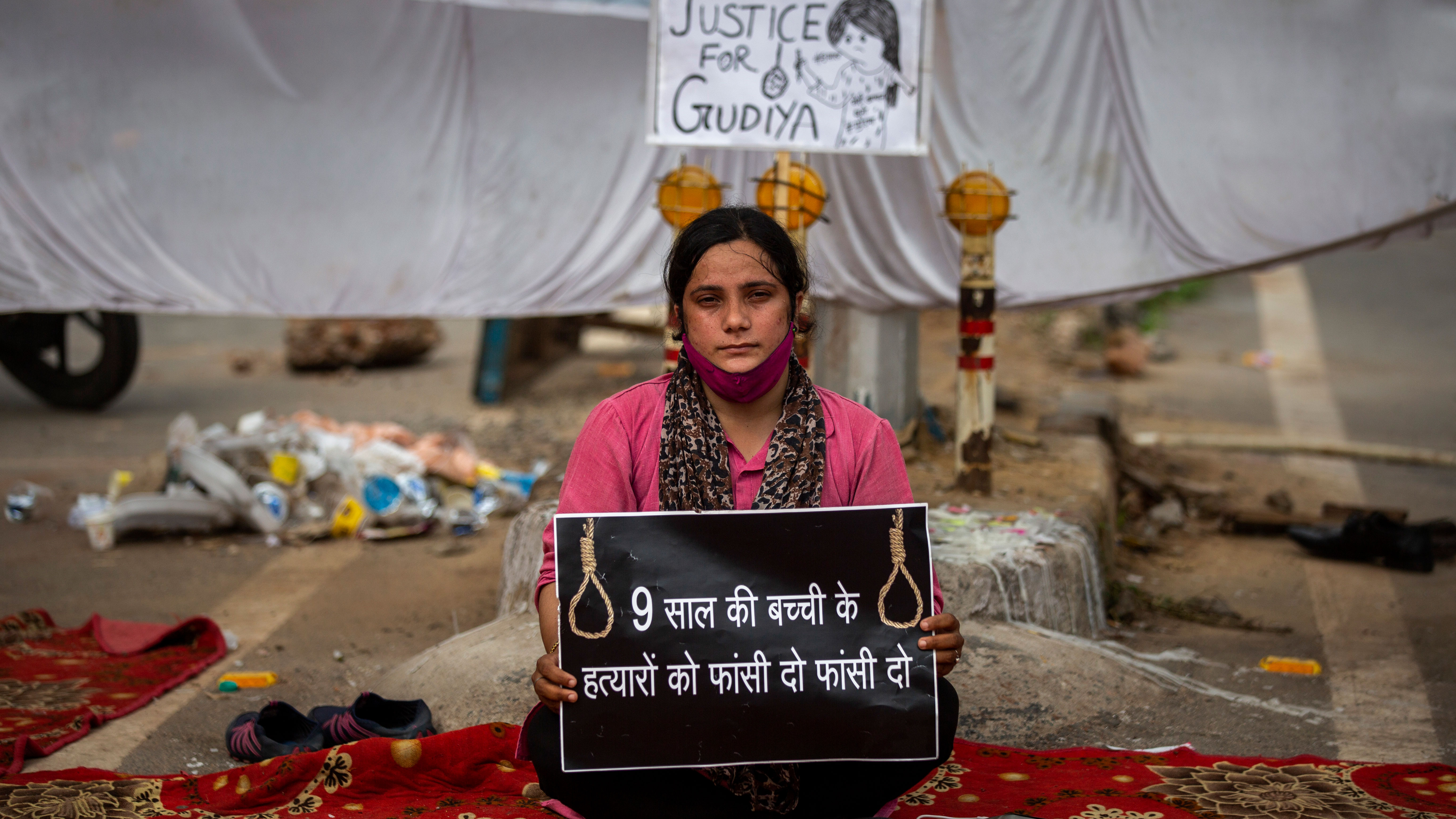 """Tina Verma, 27, a social activist, holds a placard which reads, """"Hang the killers of 9-year old child""""."""