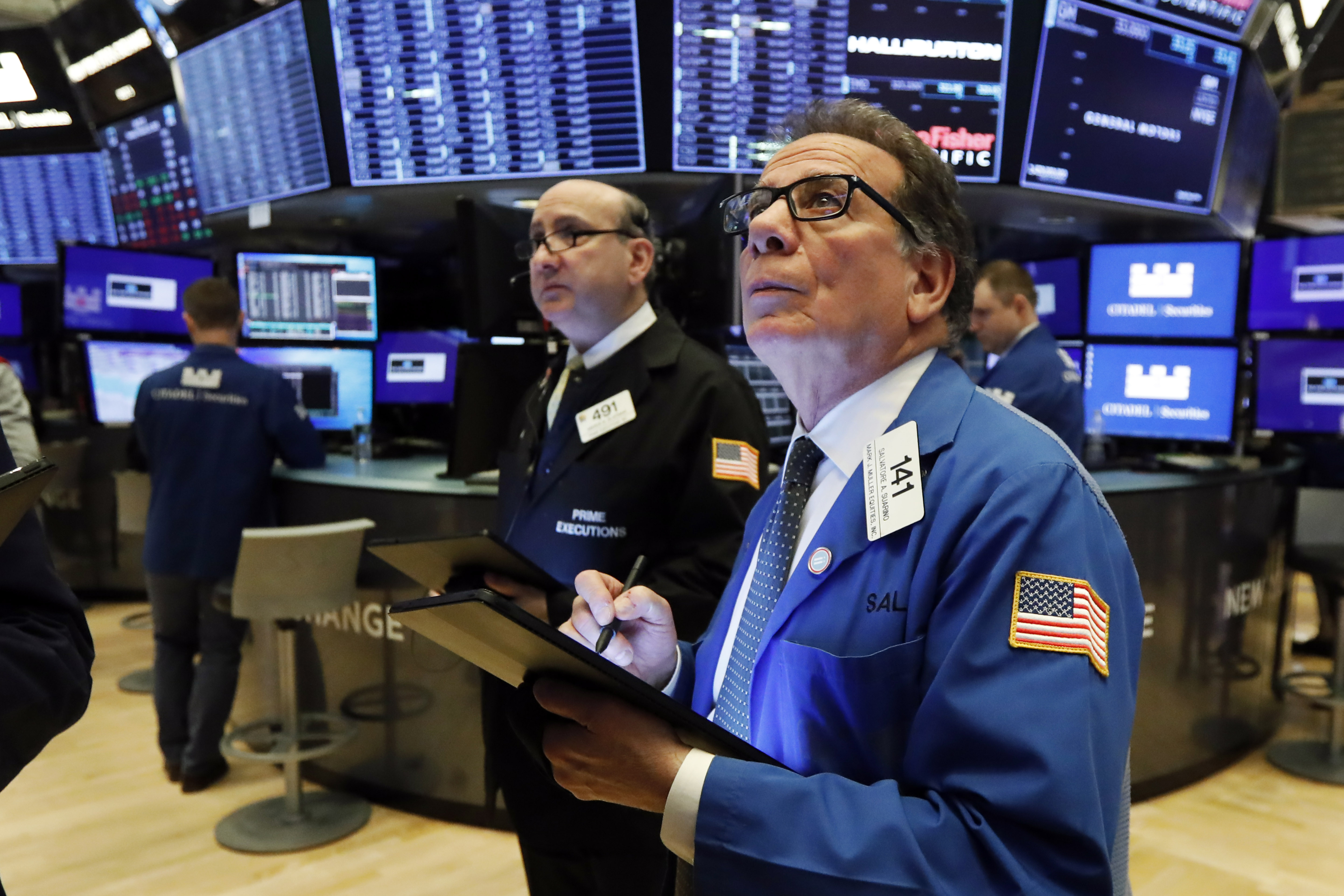 Traders work on the floor of the New York Stock Exchange after stocks hit a record low yesterday.