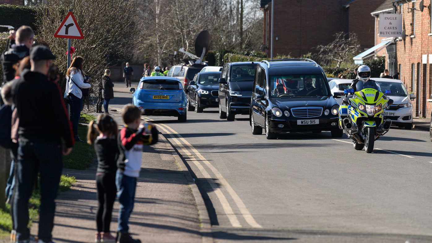 The funeral procession for Sir Tom Moore passes through the village of Marston Moretaine on the way to Bedford Crematorium ahead of a private ceremony on February 27, 2021 in Bedford, England