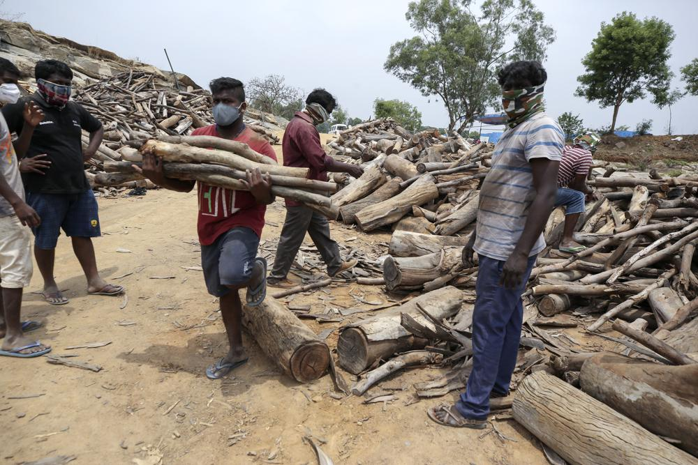 People carry wood as those who died of COVID-19 are cremated at an open crematorium on the outskirts of Bengaluru, Karnataka state, India.