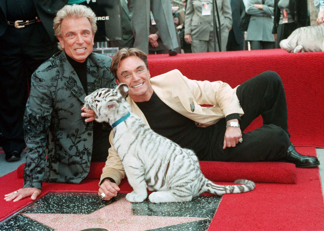 Illusionists Siegfried Fischbacher, left and Roy Uwe Ludwig Horn pose for photographers with a white tiger cub after they unveiled their star on the Hollywood Walk of Fame in Los Angeles, Calif., on Sept. 23, 1994
