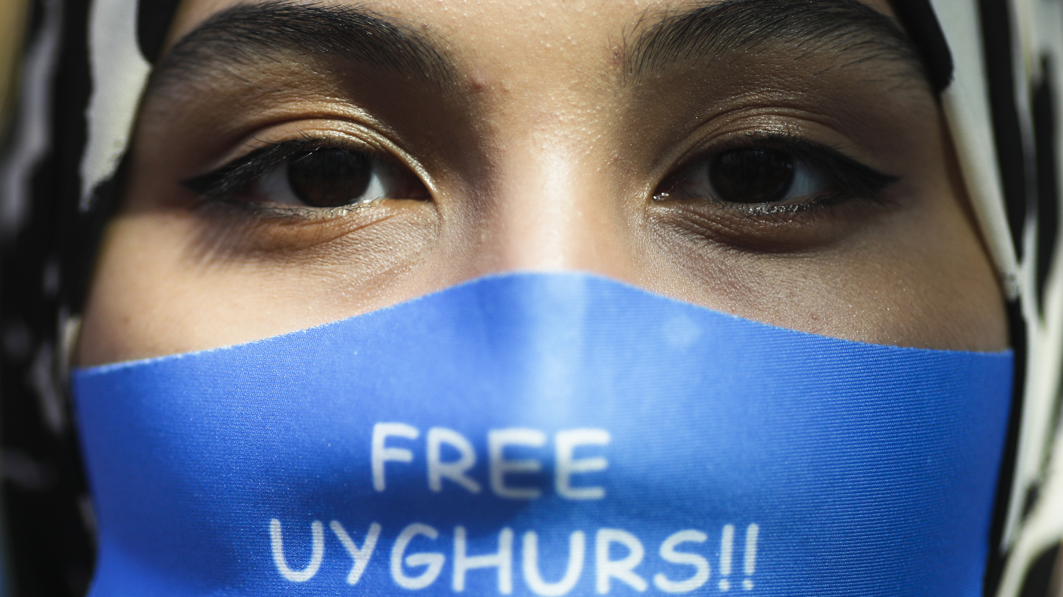 A woman wears a face mask reading 'Free Uyghurs' as she attends a protest during the visit of Chinese Foreign Minister Wang Yi in Berlin, Germany.