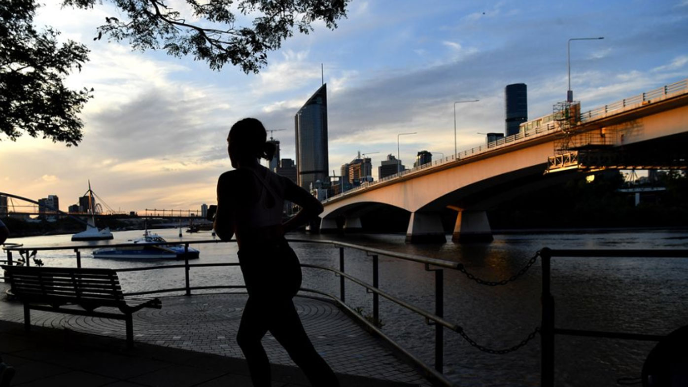 A woman jogs along the Brisbane River in Queensland.