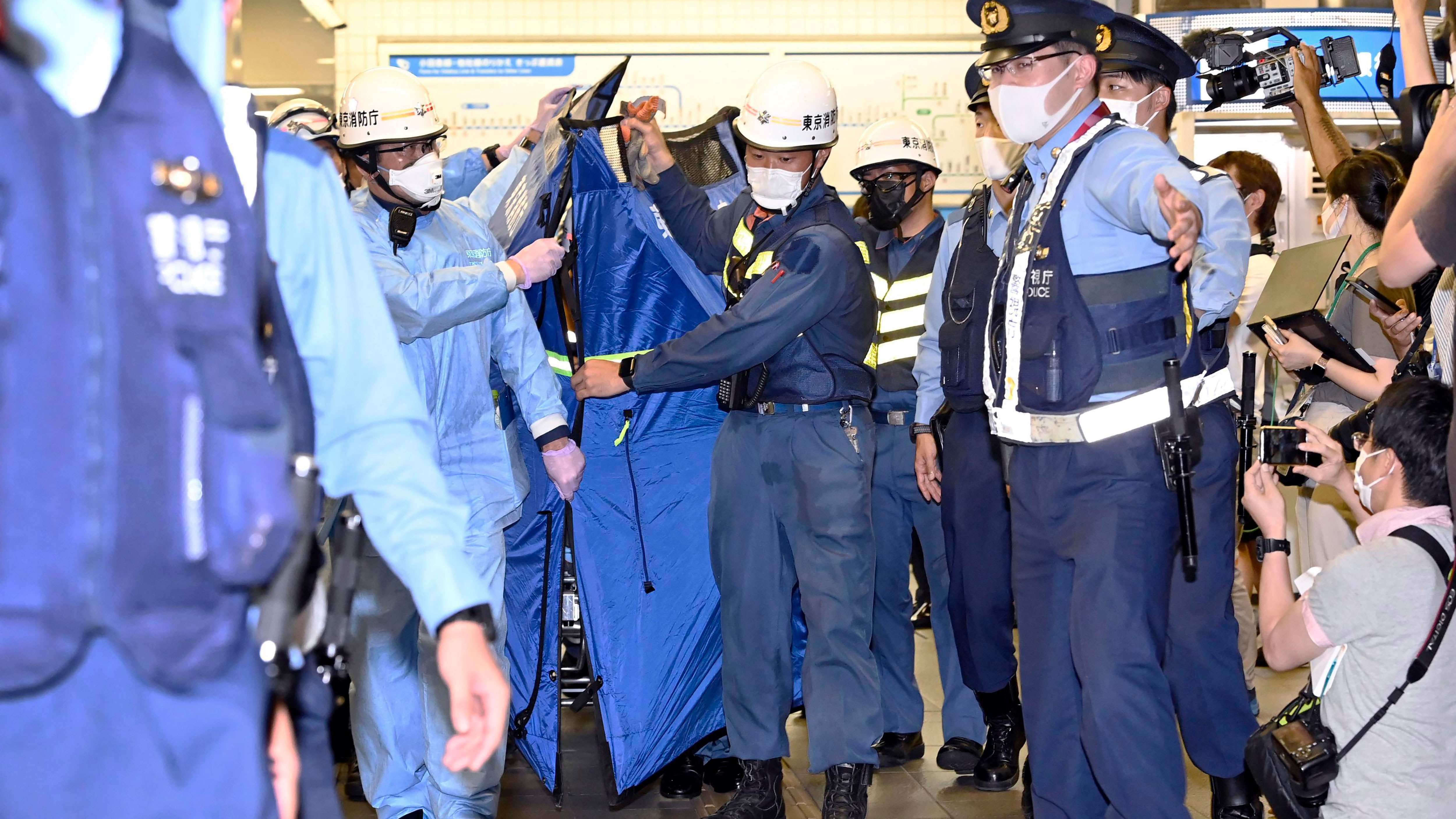 Rescuers carry a stretcher, believed to be carrying an injured passenger at Soshigaya Okura Station after stabbing on a commuter train, in Tokyo Friday night.