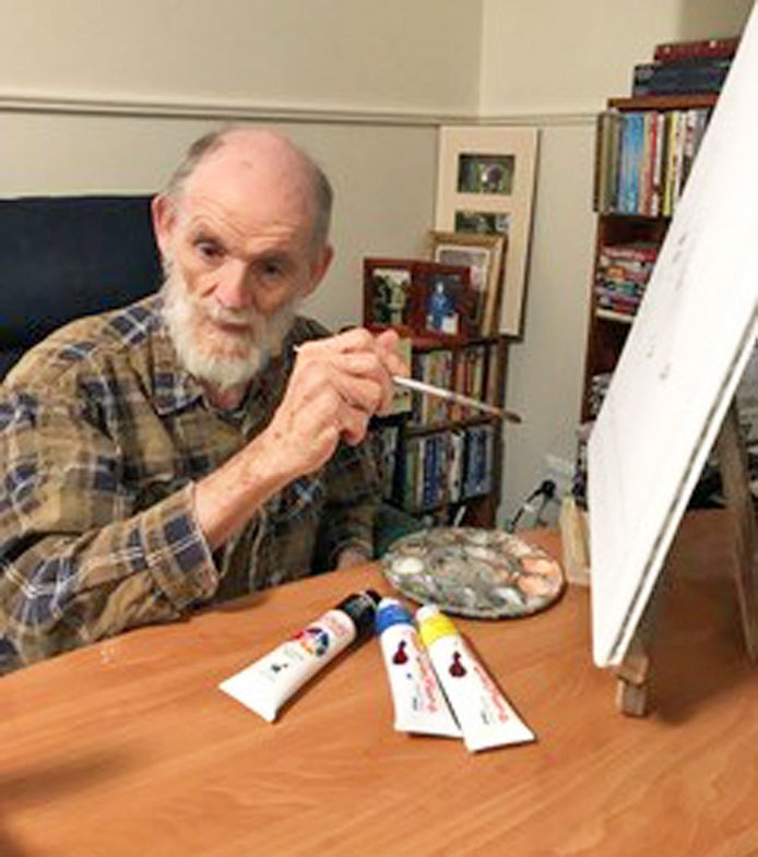 Malcolm works on his Archibald Prize entry while isolating in his room at Estia House.