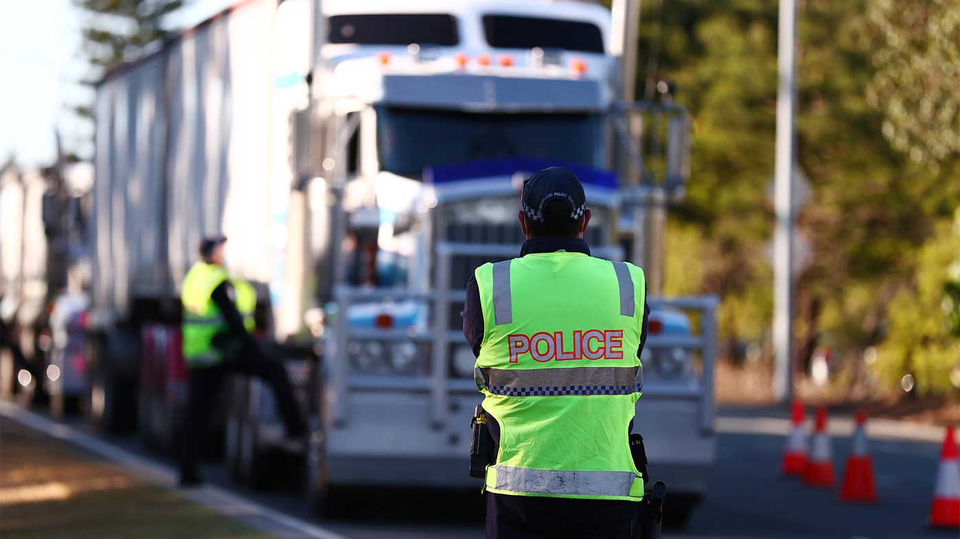 Queensland Police stop trucks at the Queensland border with NSW.