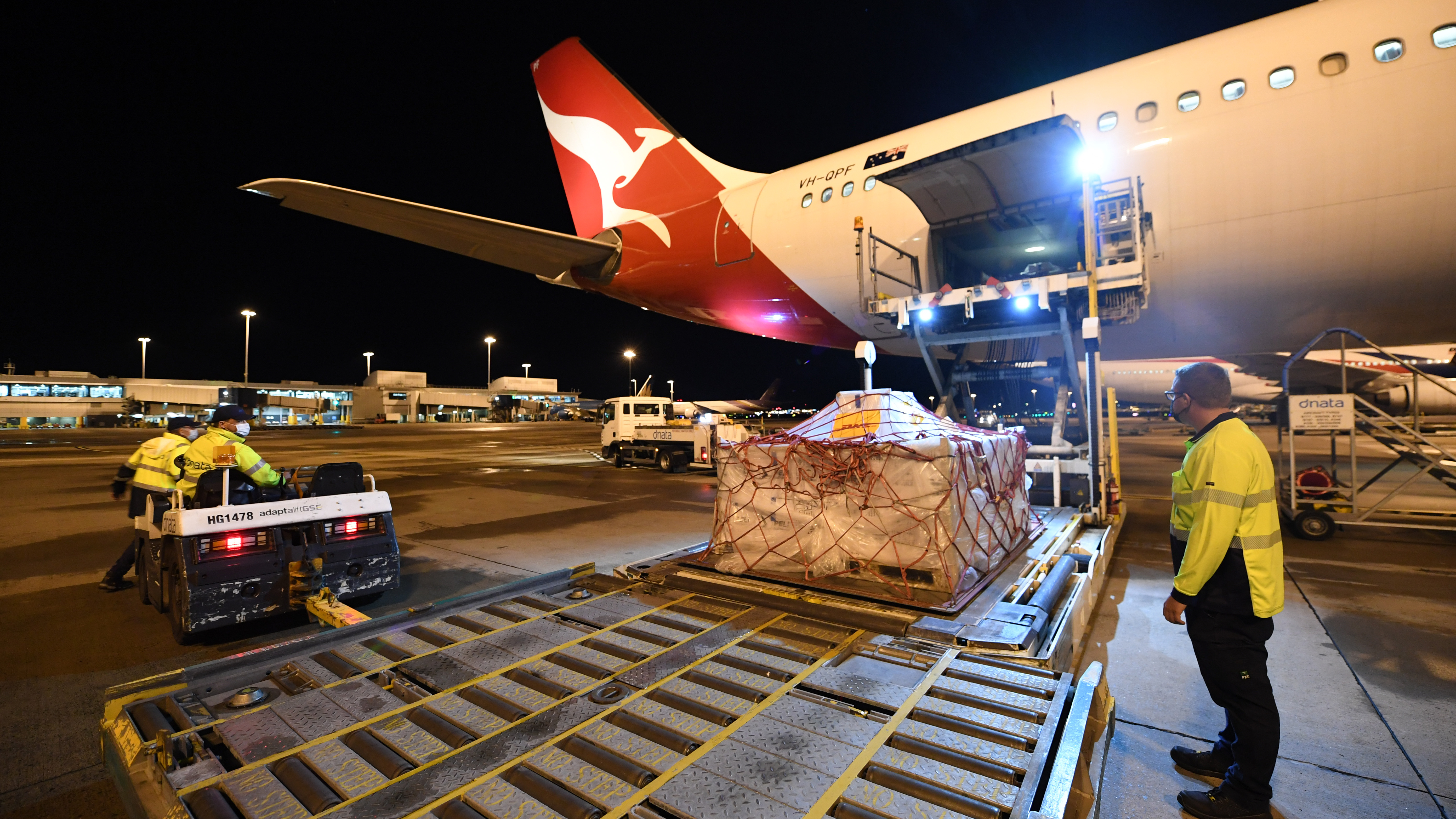 Pallets of vaccines being unloaded off Qantas flight QF110 from Darwin , which came from the UK.