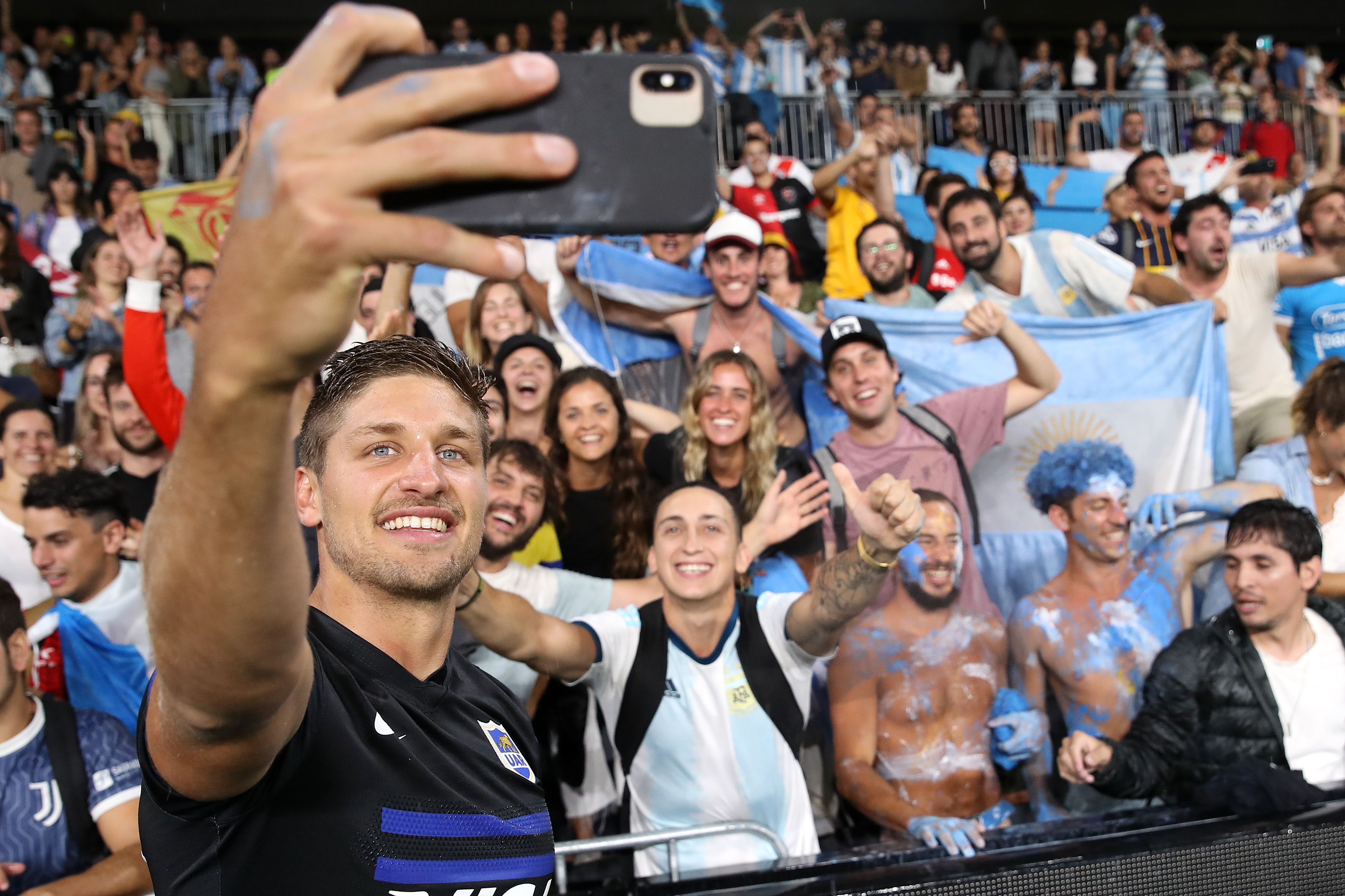 Domingo Miotti of the Pumas takes a photo with fans.