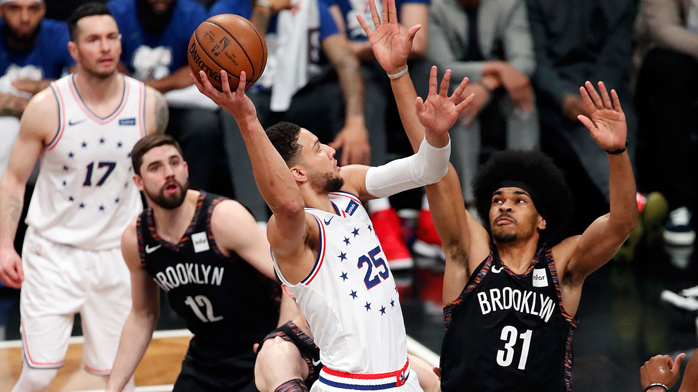 Harris watches as Simmons dunks during the NBA playoffs last season