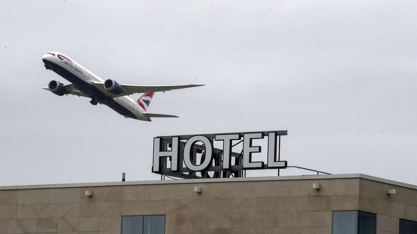 A plane passes over the Sofitel Hotel near London's Heathrow. Tuesday, Jan. 26, 2021.