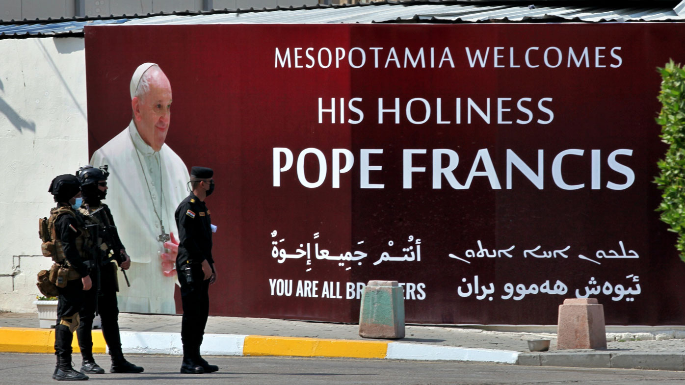 Iraqi security forces stand guard by a mural depicting Pope Francis outside of Our Lady of Salvation Church in Baghdad, Iraq, Friday, March 5, 2021