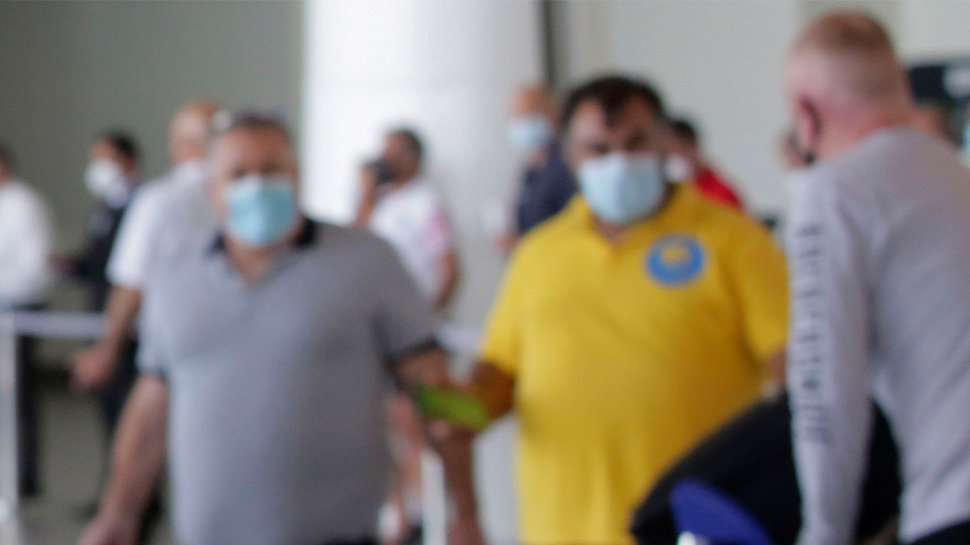 Blurred passengers at airport wearing face masks.