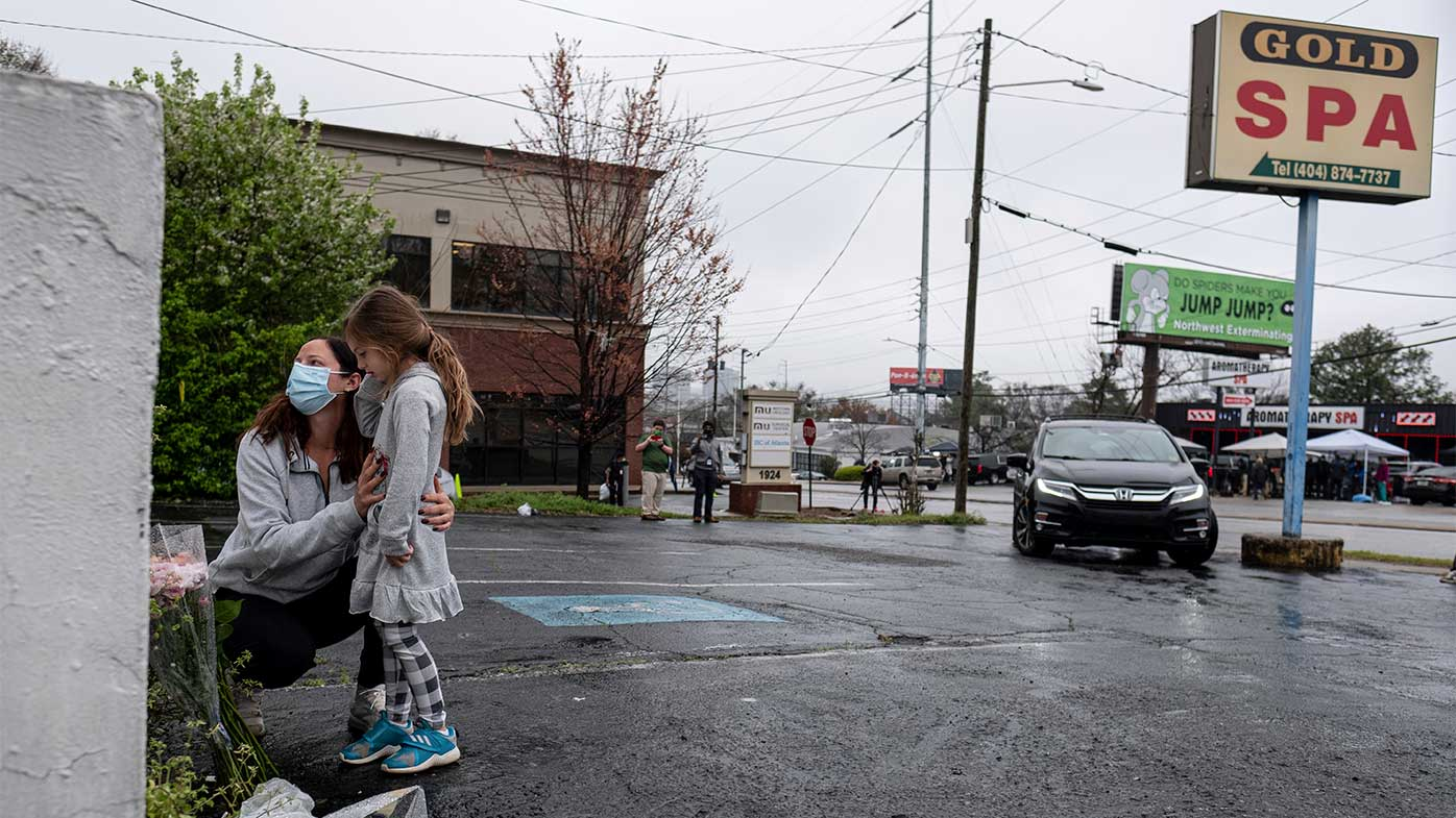 Mallory Rahman and her daughter Zara Rahman, 4, who live nearby, pause after bringing flowers to the Gold Spa massage parlor in Atlanta.