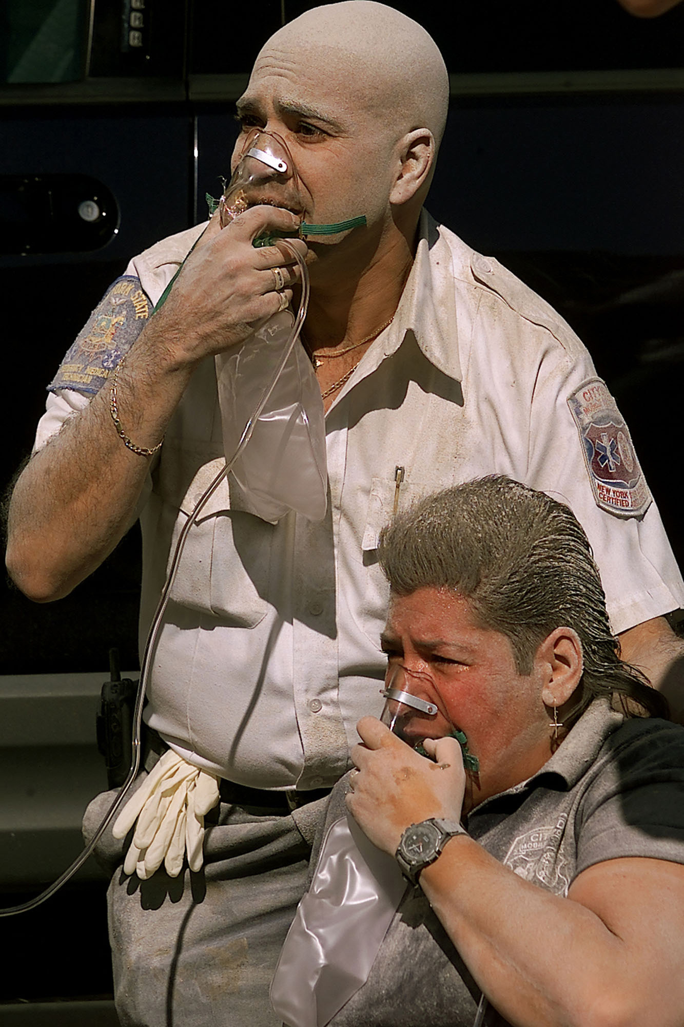A paramedic and a policemen breath oxygen after the South Tower crumbled down.