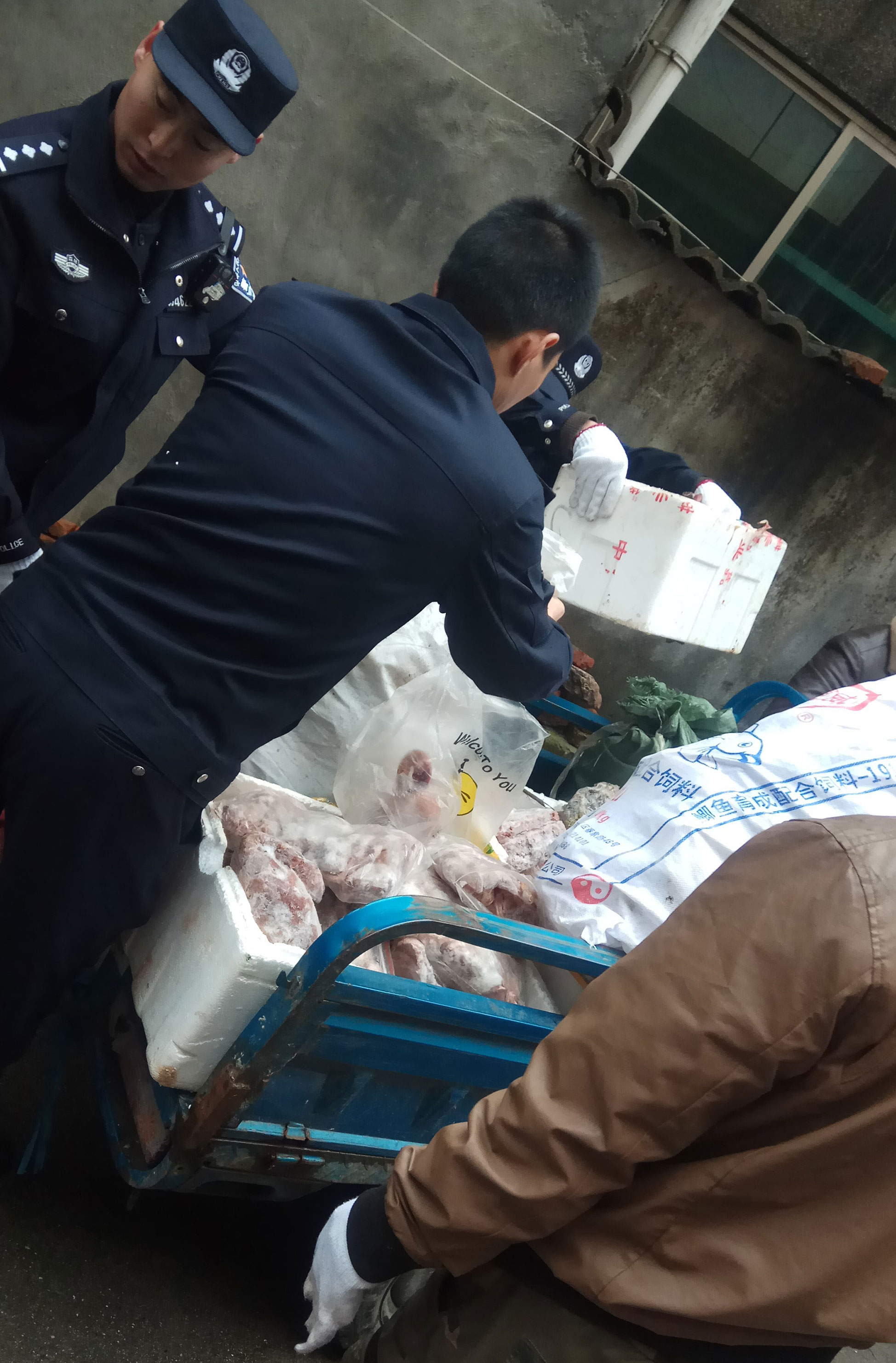 Police load a cart with items seized from a store suspected of selling trafficked wildlife are seen in Anji city in eastern China's Zhejiang Province.