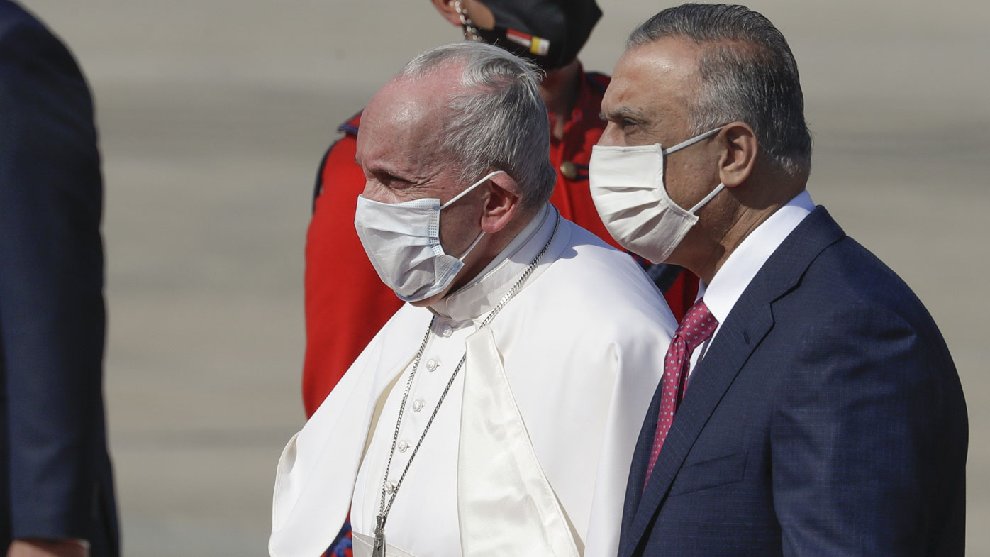 Pope Francis is flanked by Iraqi Prime Minister Mustafa al-Kadhimi upon hi arrival at Baghdad's international airport, Iraq, Friday, March 5, 2021