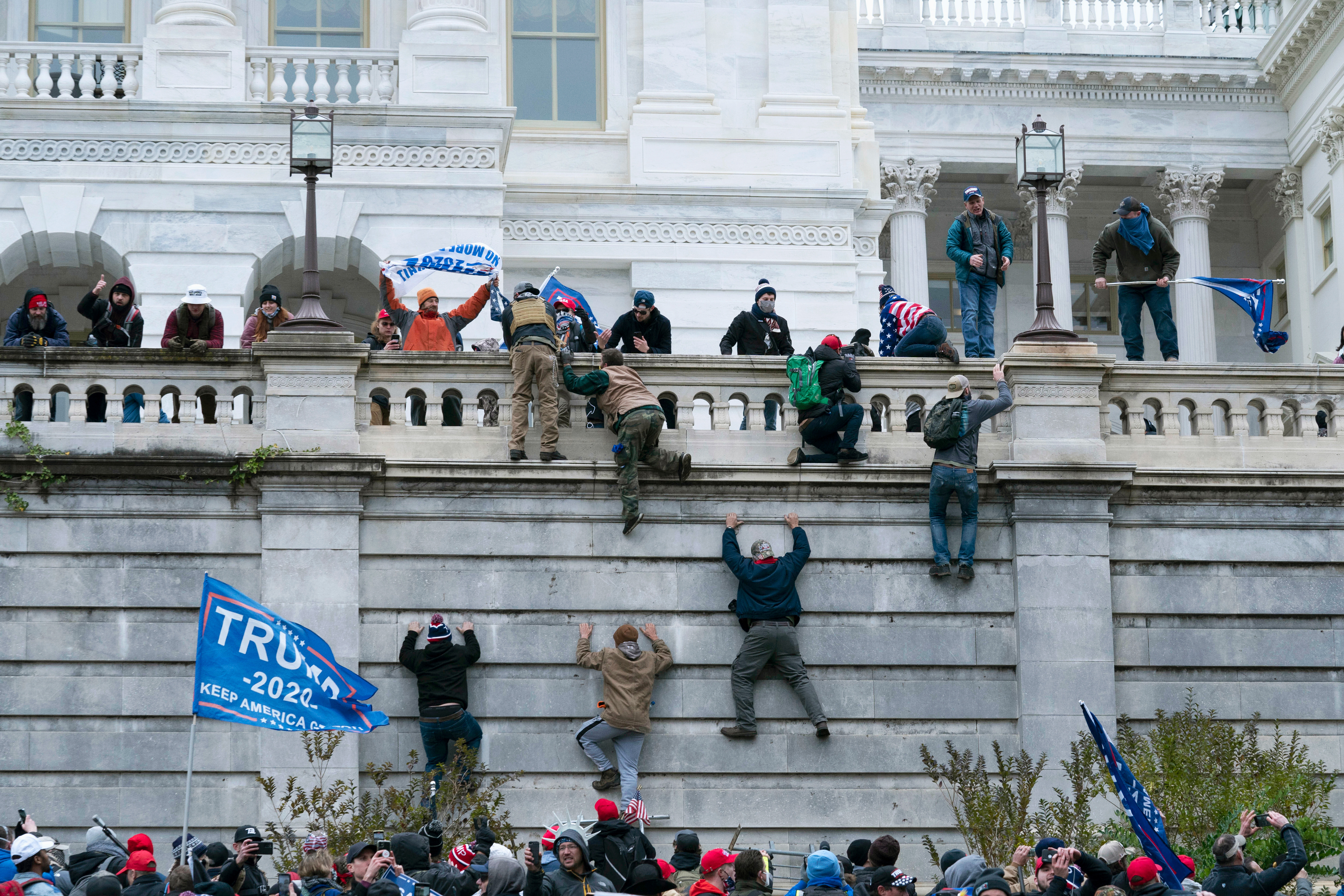 Rioting supporters of President Donald Trump climb the west wall of the the US Capitol in Washington.