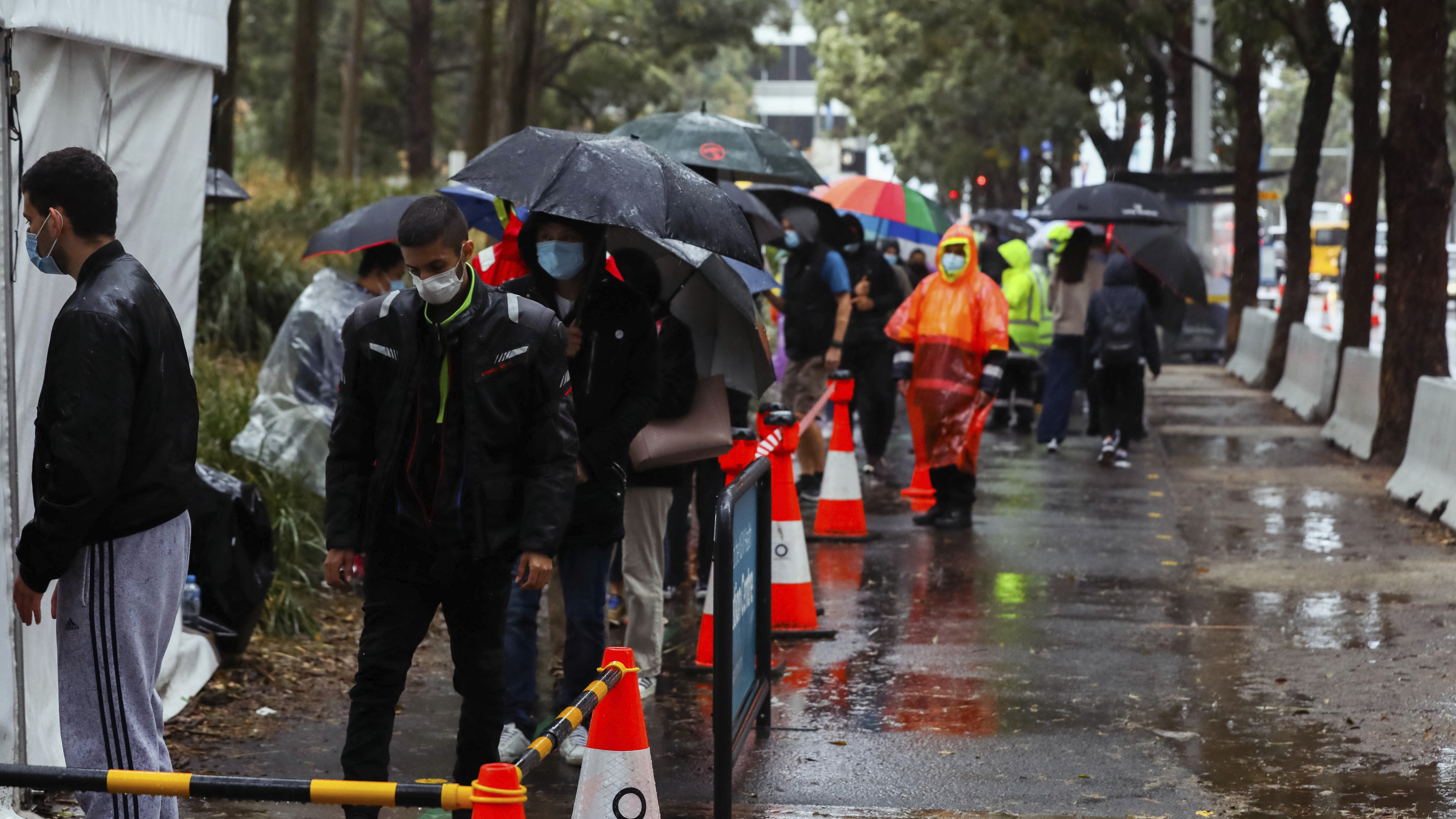 People line up to receive their covid-19 vaccination despite wet weather at the Sydney Olympic Park Vaccination Centre in Sydney.