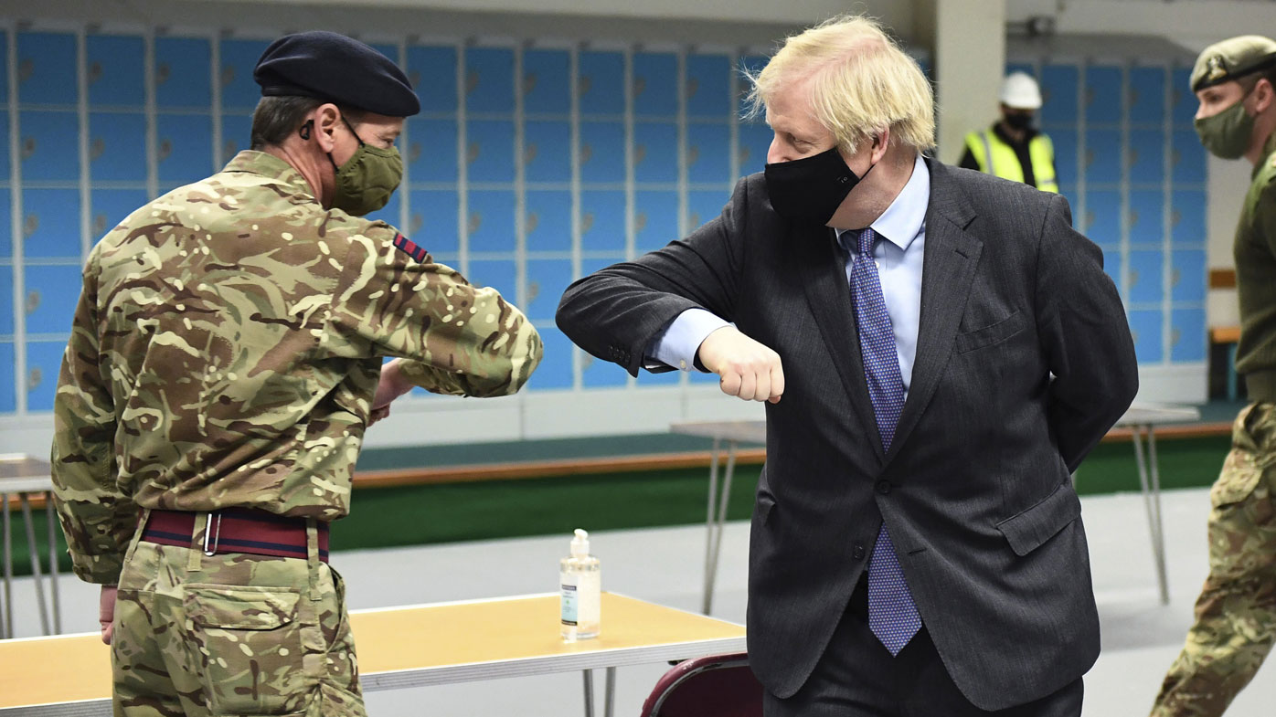 Britain's Prime Minister Boris Johnson elbow bumps a member of the military as he meets troops setting up a vaccination centre in the Castlemilk district of Glasgow, on his one day visit to Scotland, Thursday, Jan. 28, 2021.
