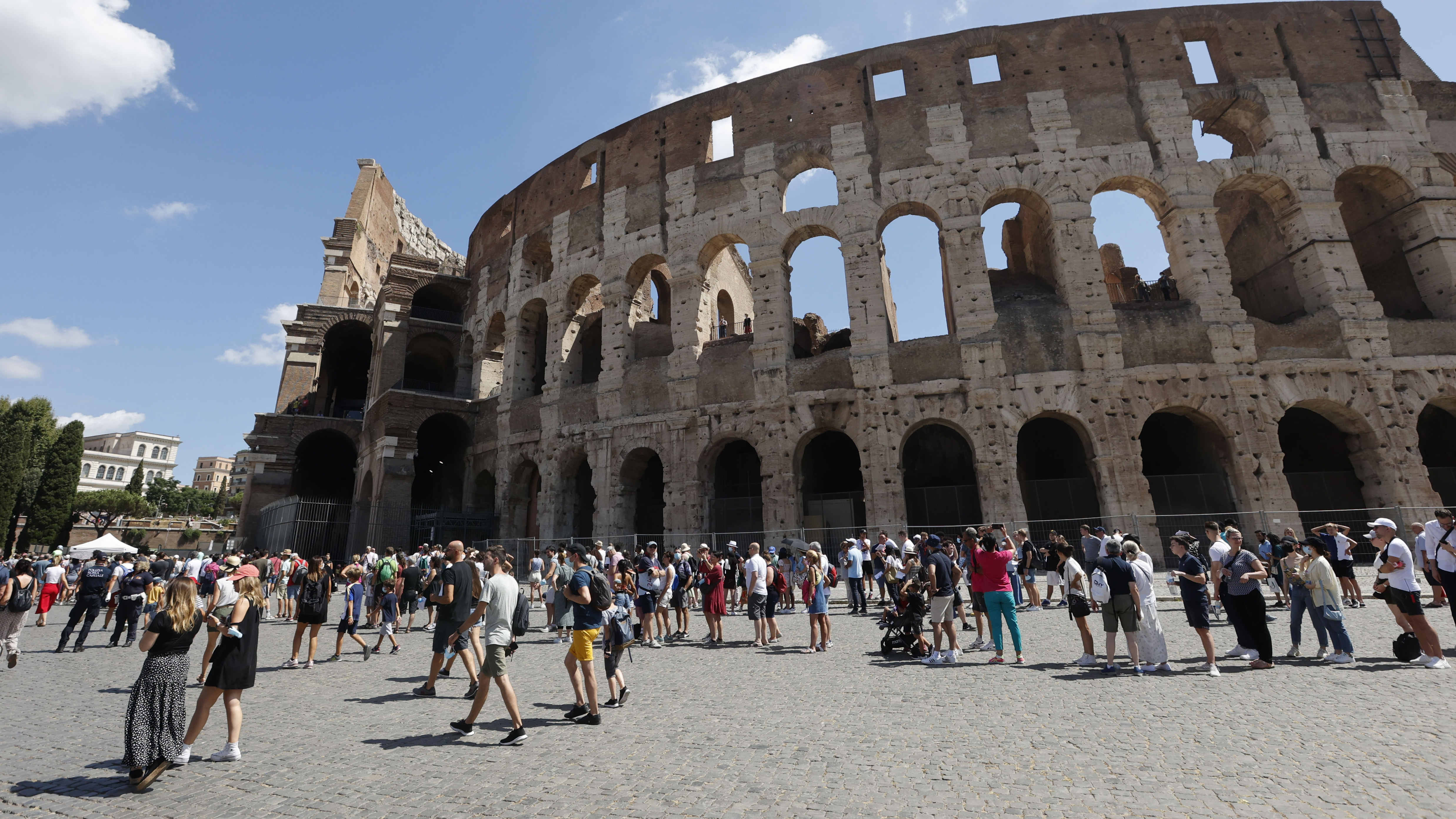Tourists wait in a queue to enter the Colosseum in Rome, Italy.