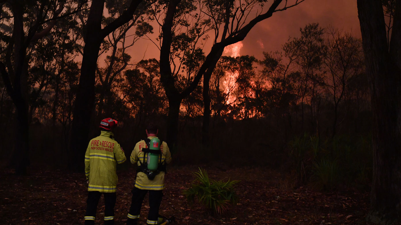 Fire fighting crews from the RFS, NSW Fire and Rescue and NPWS officers fight a bushfire encroaching on properties near Lake Tabourie on the Princes Highway between Bateman's Bay and Ulladulla south of Sydney,Thursday, December, 5, 2019