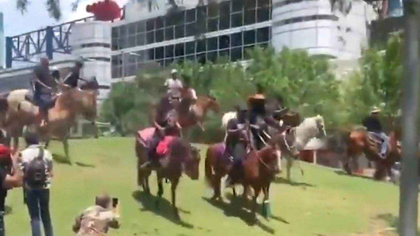 Horsemen and women ride down a bank in Houston, during a George Floyd march.