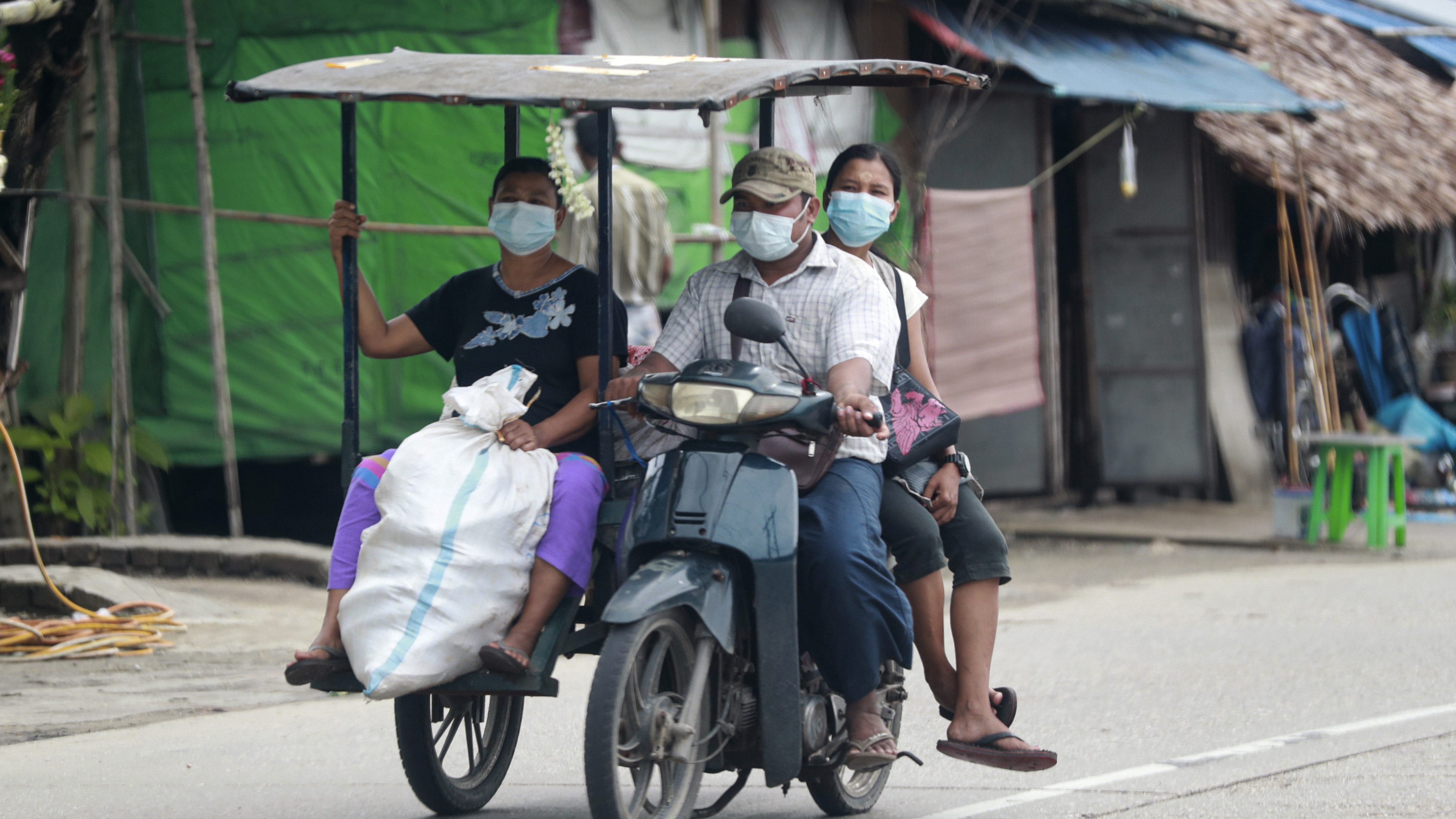 In this July 28, 2021, file photo, people wearing face masks to help curb the spread of the coronavirus ride a tricycle to transport goods in Shwe Pyi Thar township in Yangon, Myanmar.