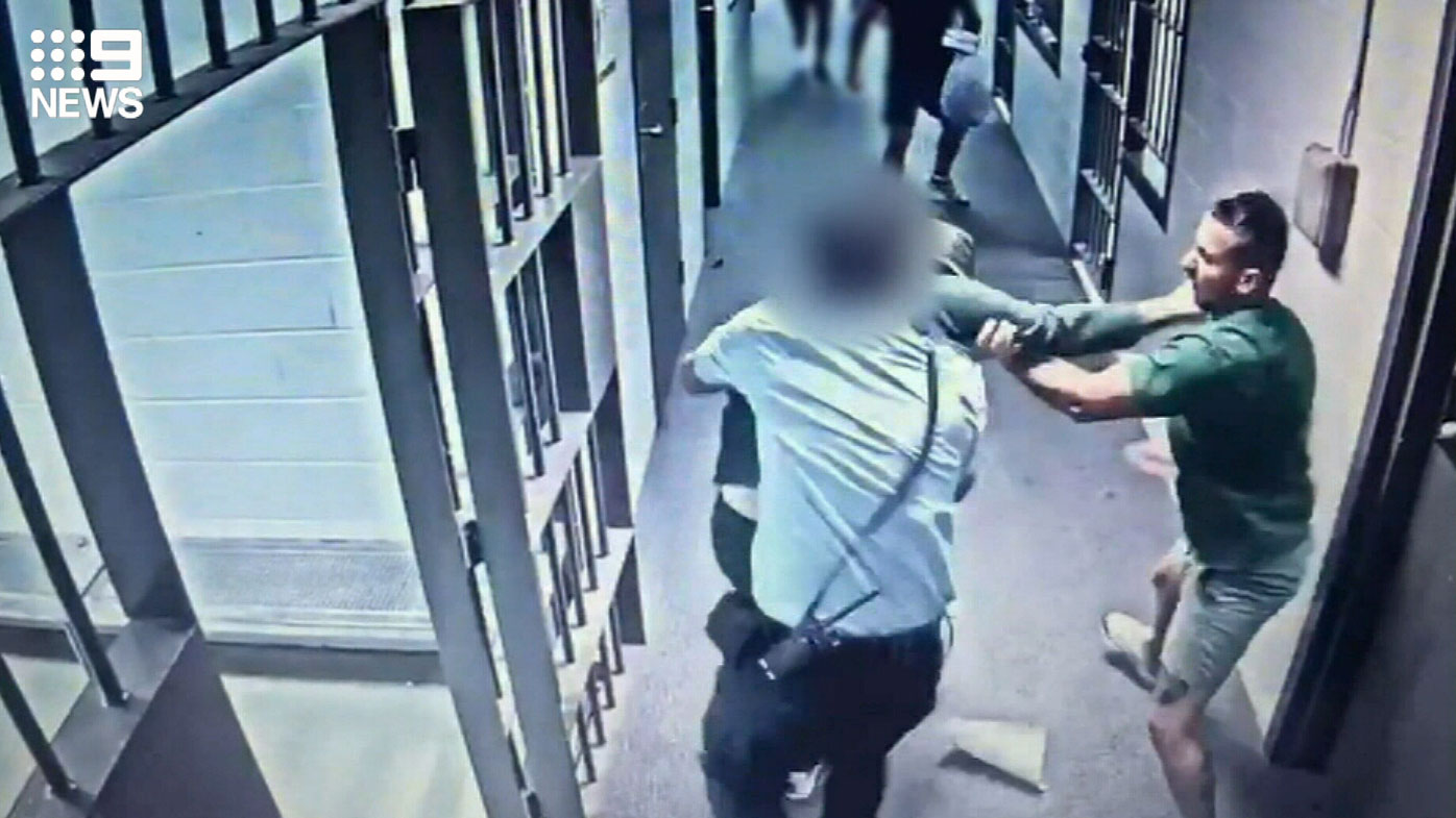 A prison officer throws himself between the pair.