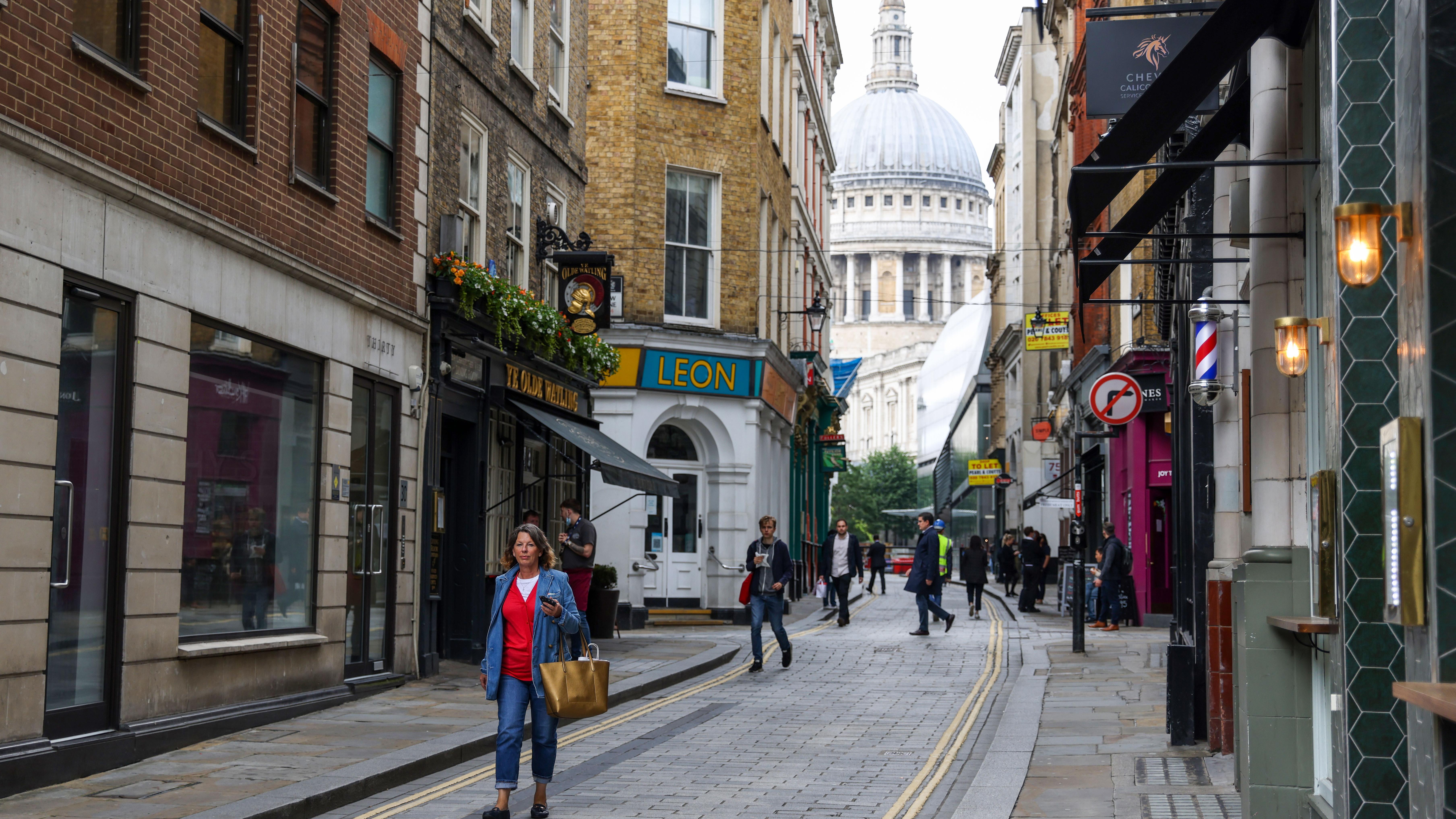A pedestrian walks along Watling Street in view of St. Paul's Cathedral in London.