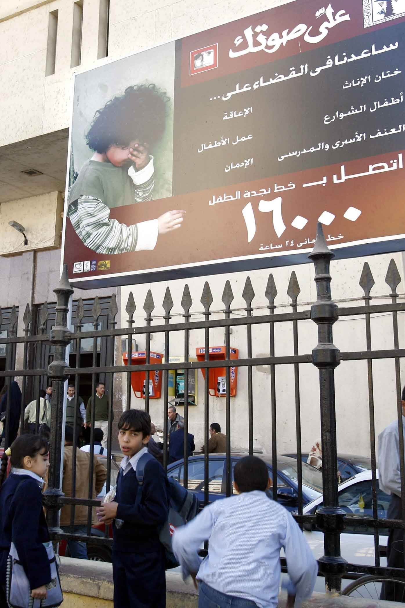 Egyptian children walk under a billboard, that is part of a national campaign to encourage families to stop circumcising their daughters.