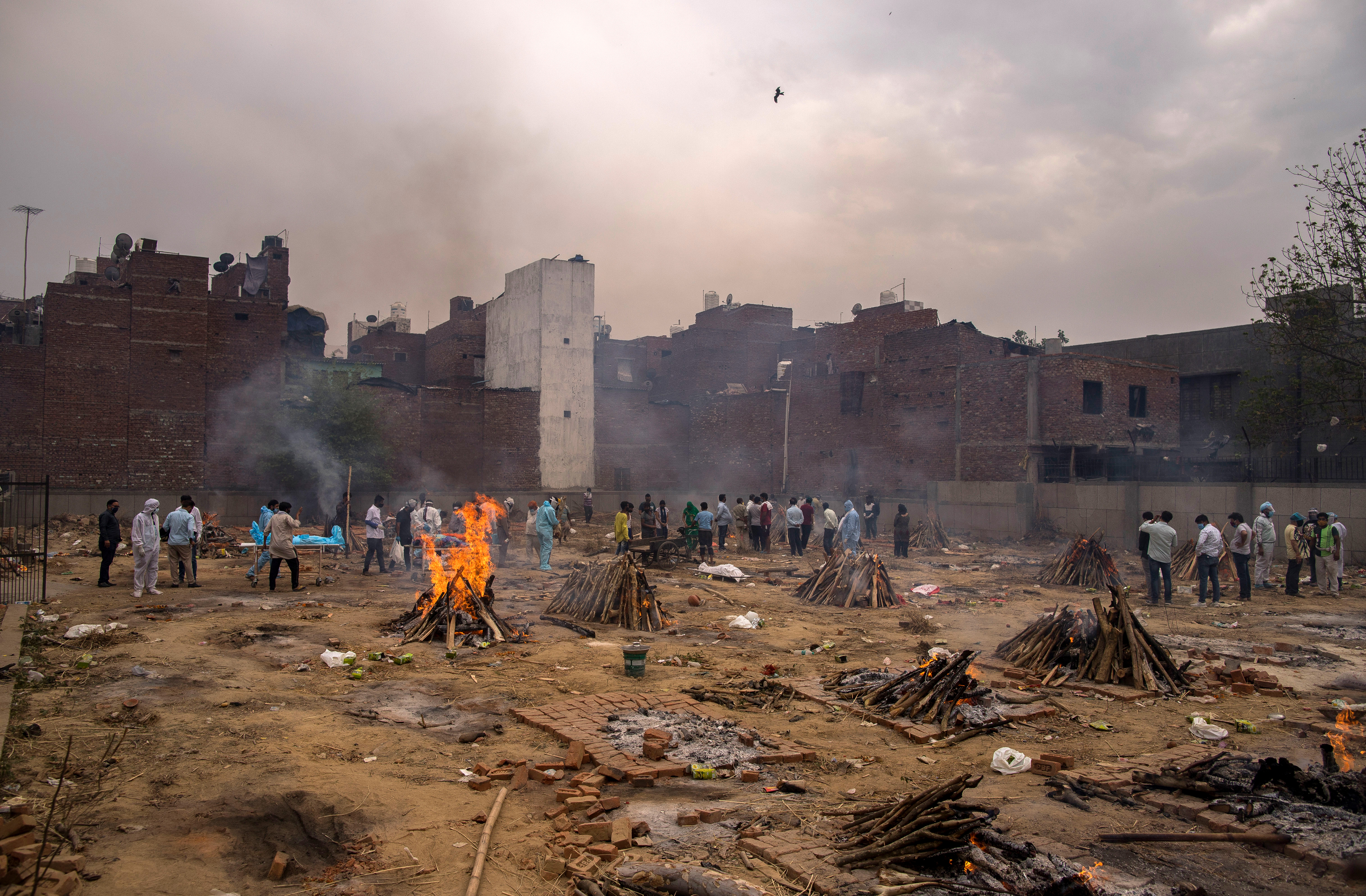 Multiple funeral pyres burn at a ground converted into a makeshift crematorium in New Delhi, India.
