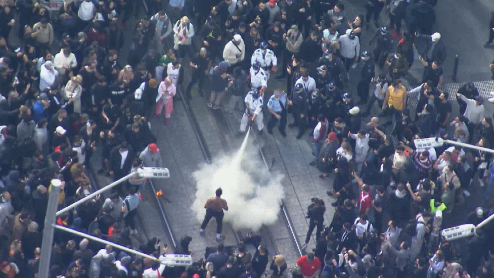 The man had his fire extinguished and then appeared to be held by police.