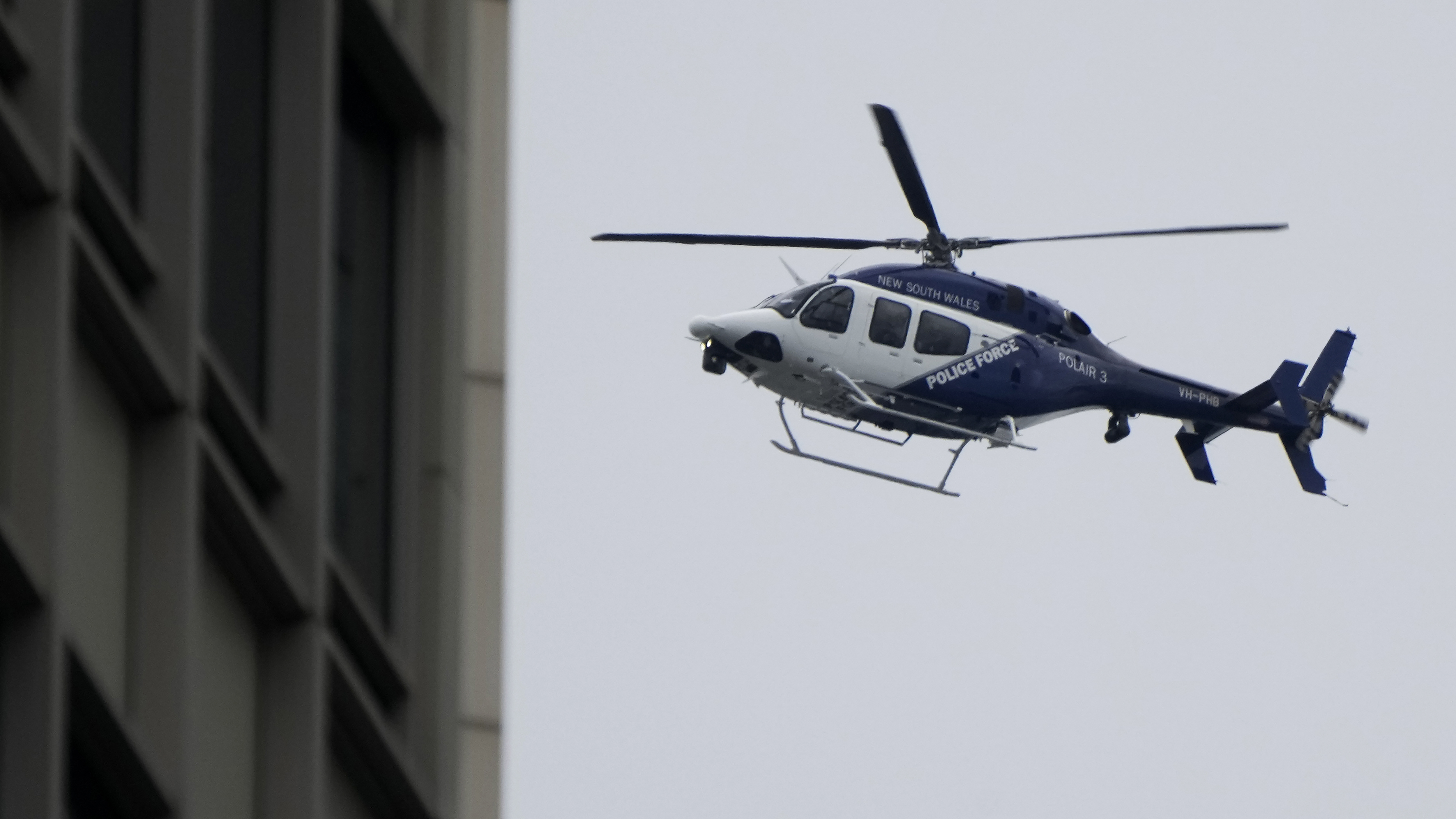 A New South Wales police helicopter patrols the sky over the central business district in Sydney.