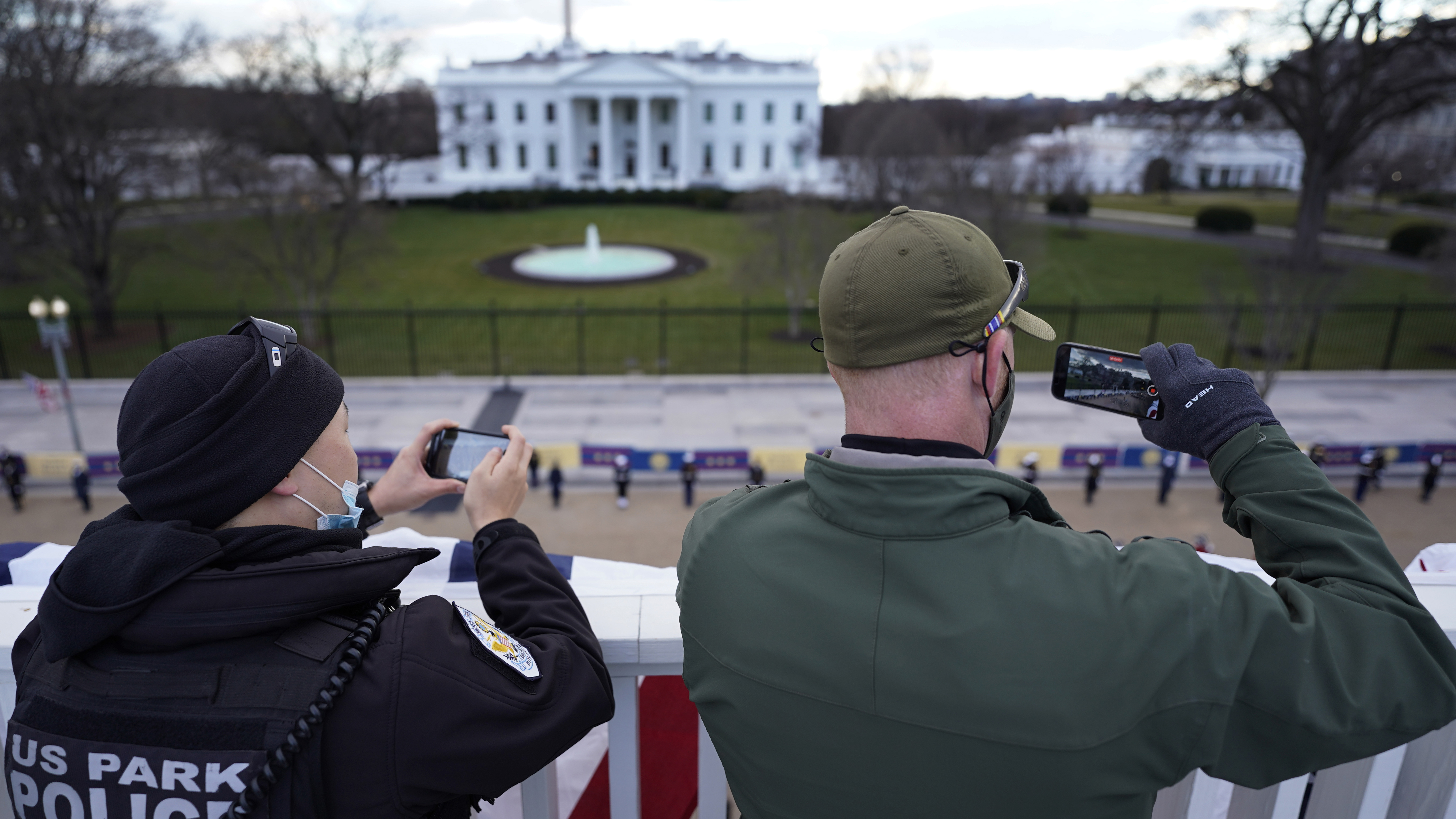 Police take photos as a ceremonial guard marches past the White House during a rehearsal for the President-elect Joe Biden's inauguration ceremony.