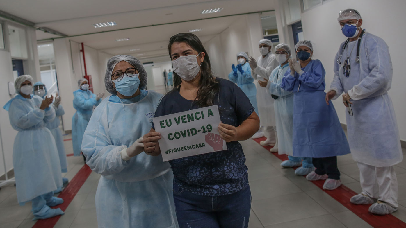 """After 10 days of treatment for coronavirus, Kelly Araujo de Andrade holds a sign that reads """"I beat the COVID-19 #StayAtHome"""" while she walks through the main hall followed by a chief nurse leaving the Gilberto Novaes Municipal Field Hospital, in Manaus, Brazil."""