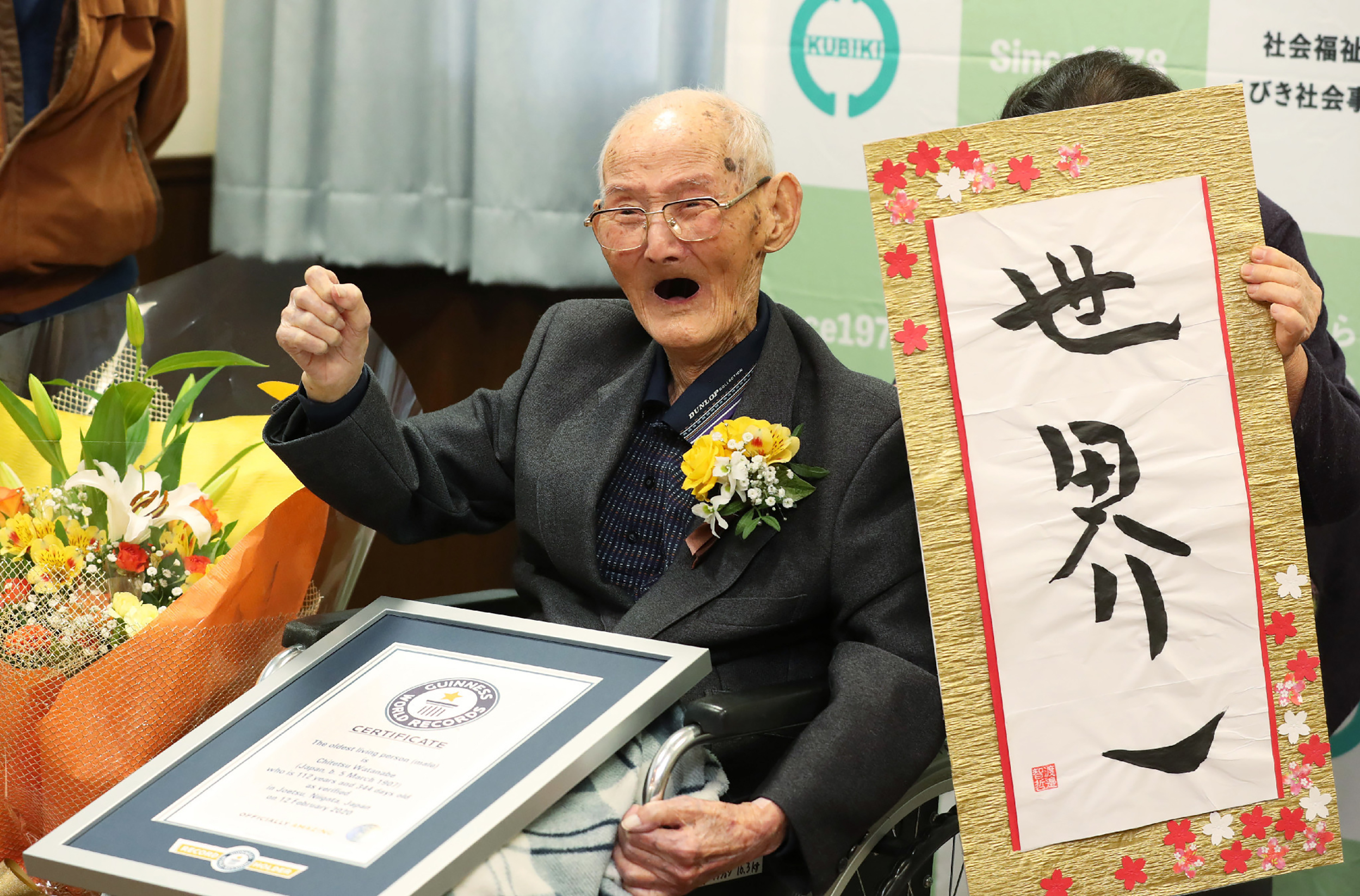 Chitetsu Watanabe poses next to calligraphy reading in Japanese 'World Number One' after he was awarded as the world's oldest living male in Joetsu, Niigata.
