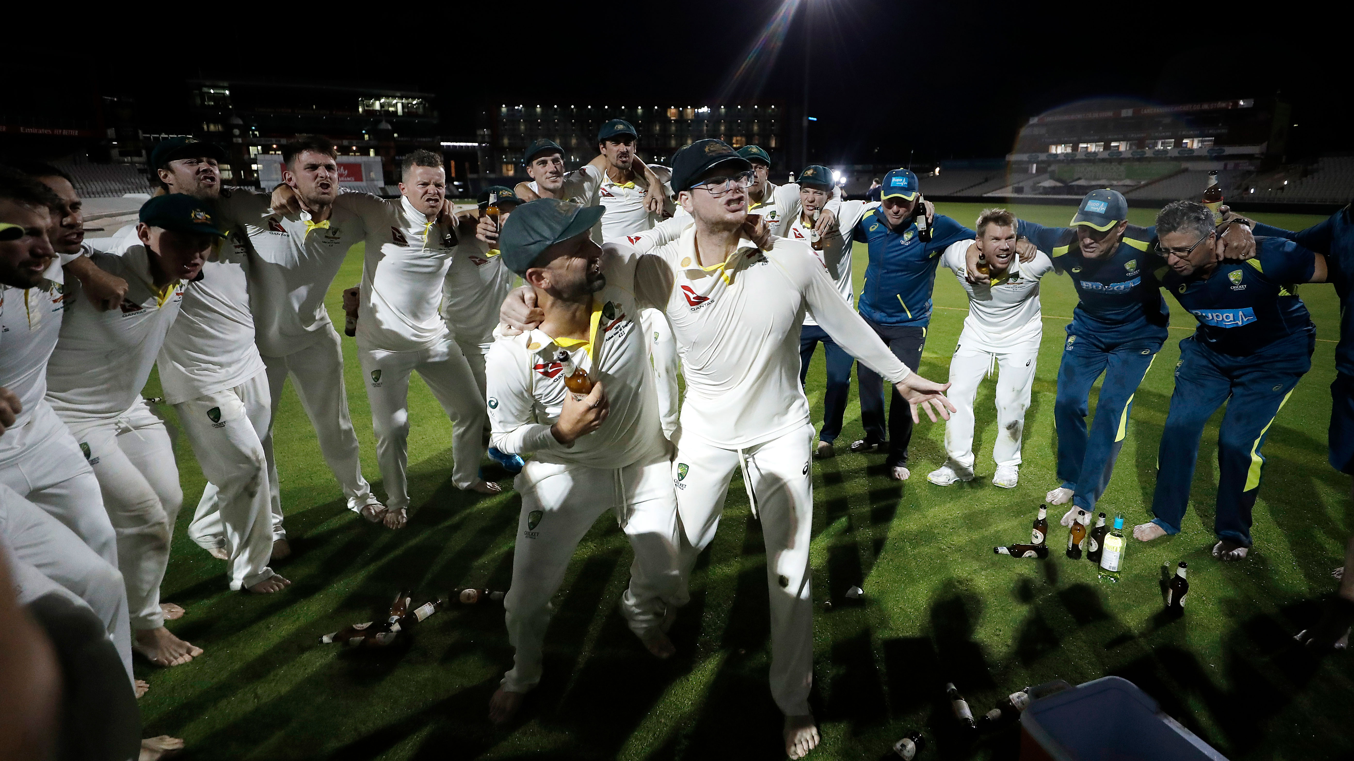 Nathan Lyon and Steve Smith belt out the victory song together in the middle of the Old Trafford pitch, surrounded by teammates.