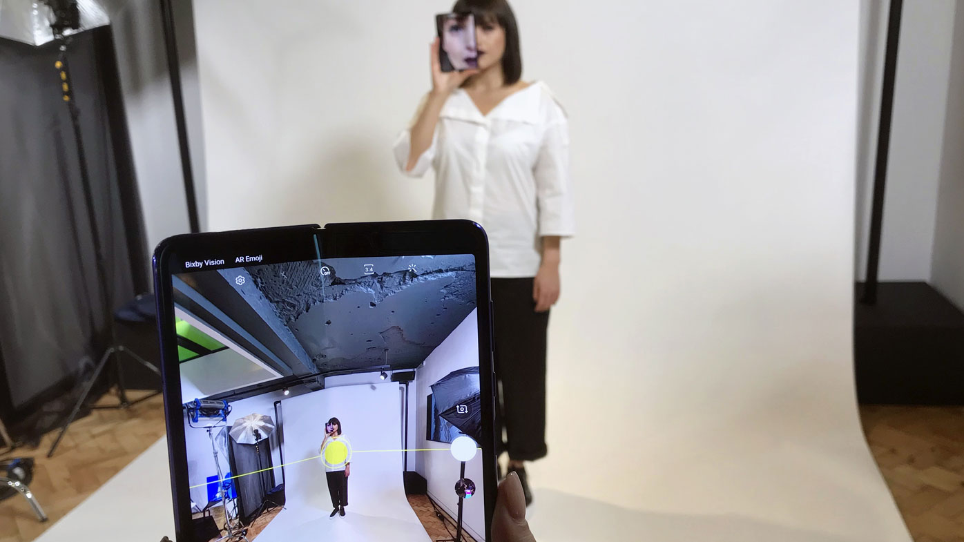 A model holds a Samsung Galaxy Fold smart phone to her face, during a media preview event in London.