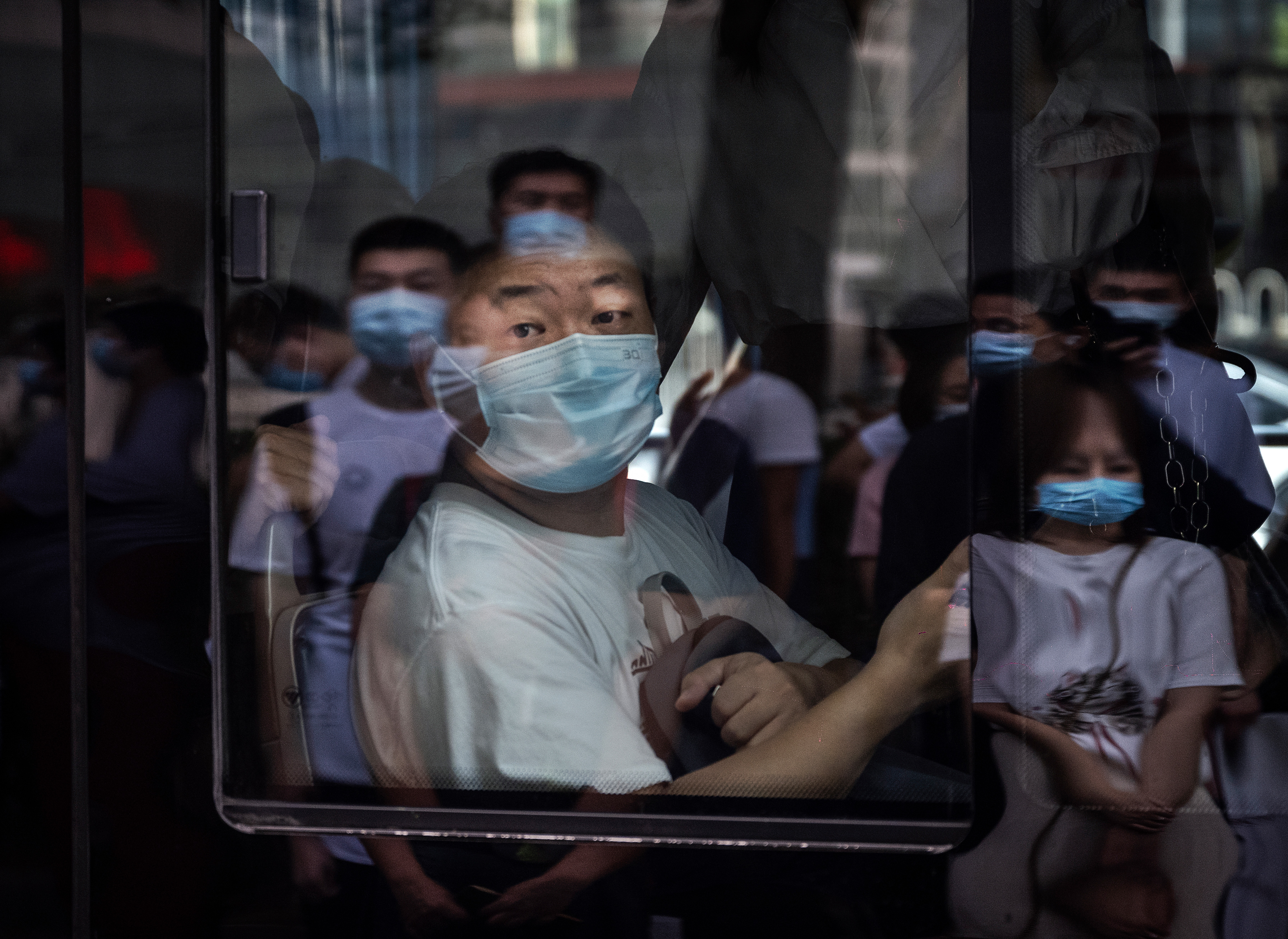 A commuter wears a mask to protect against COVID-19 as he sits on a public bus in Beijing.