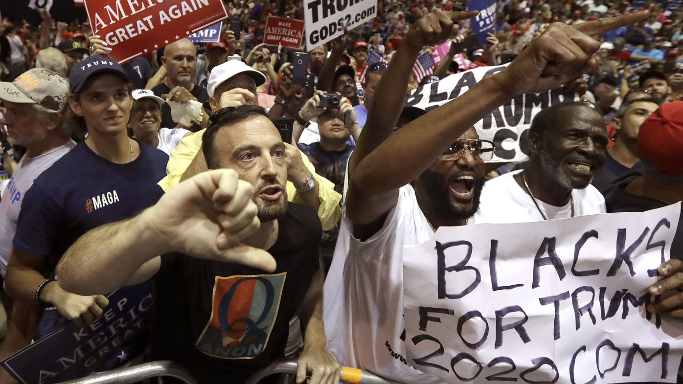 A man wearing a QAnon shirt jeers at a CNN reporter at a Donald Trump rally.